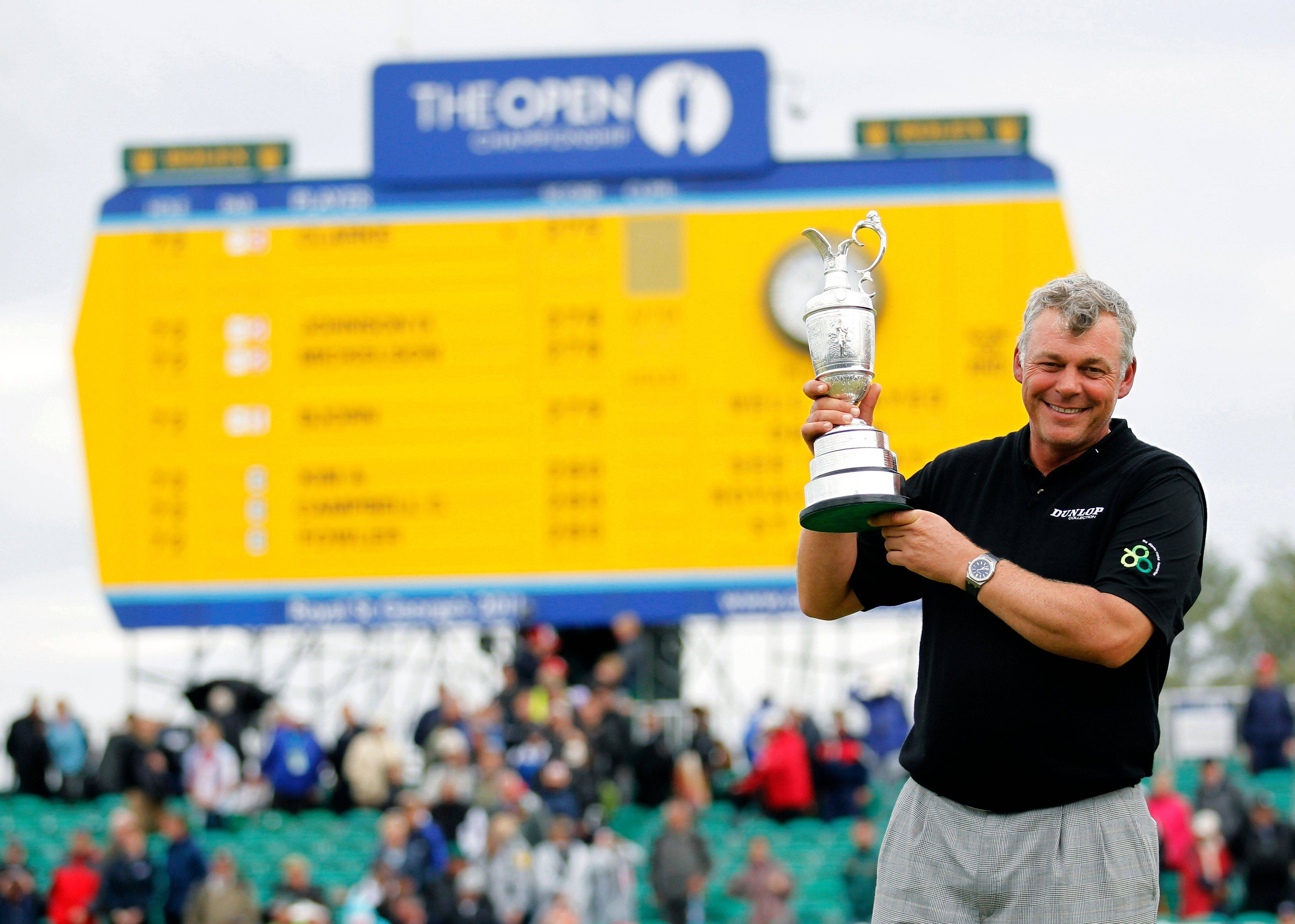 Northern Ireland's Darren Clarke holds the Claret Jug trophy in front of the scoreboard on the 18th green as he celebrates winning the British Open Golf Championship at Royal St George's golf course Sandwich, England, Sunday.