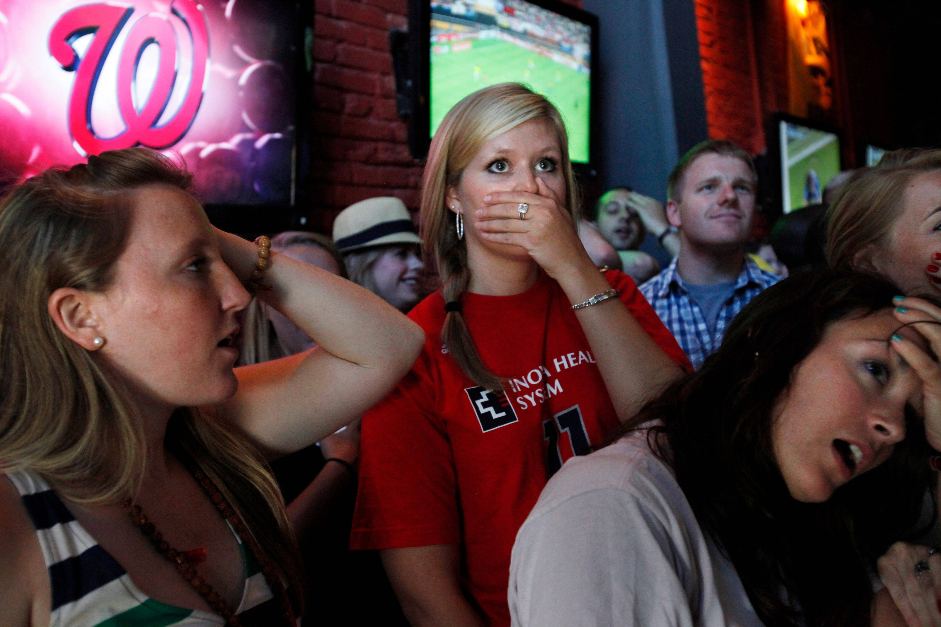 Soccer fan Leigh Ann Renfro, center, reacts after Japan scored, tying the United States during the second half of the Women's World Cup soccer final, as fans watch at Public Bar in Washington on Sunday.