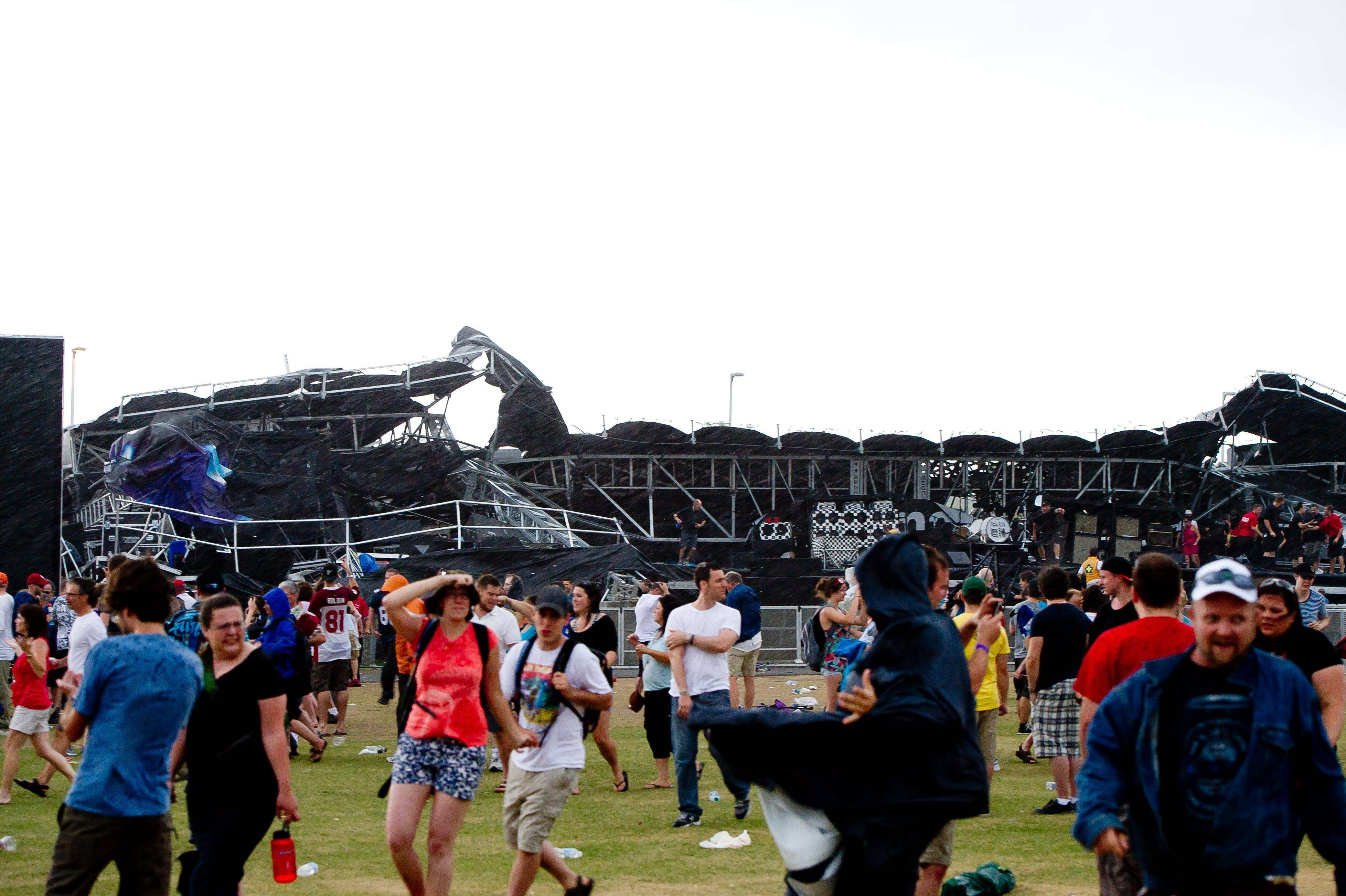 People run for cover after the main stage at the Ottawa Bluesfest collapsed Sunday, July 17, in Ottawa, Ontario, when a severe thunderstorm swept through the area.