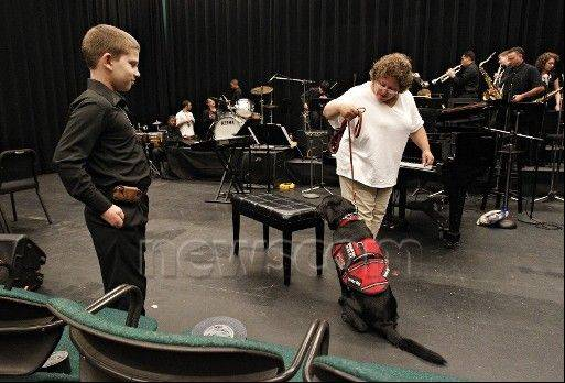Billy Gensel counts on service dog Remy to detect any trace of peanuts, to which he's acutely allergic. His mom, Karen, guides the dog, which sits to indicate possible danger. Wiping down the piano bench with alcohol eliminates the threat so Billy can play with the Patel Conservatory Jazz Ensemble.