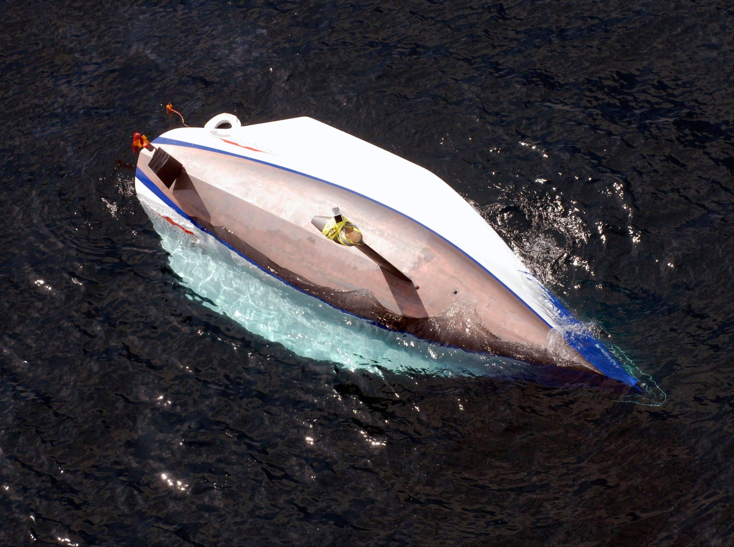 The sailboat WingNuts floats upside down in Lake Michigan on Monday after it capsized during the annual Chicago-to-Mackinac sailing race. Two crew members died.