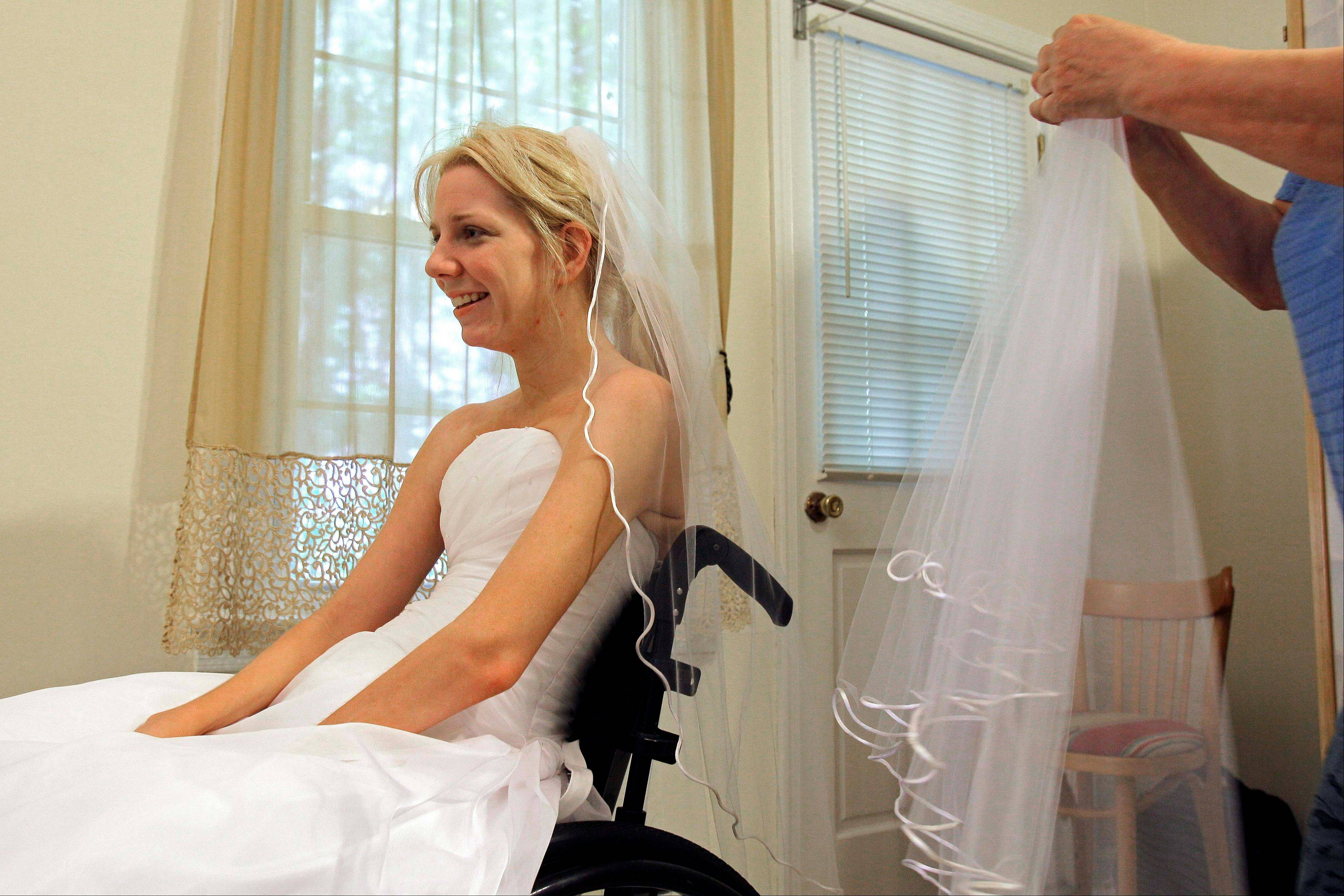 Rachelle Friedman tries on a veil during the fitting for her wedding dress. She was left paralyzed after a swimming pool accident that postponed her wedding plans. But a year later, she is ready for her trip to the altar on Friday.