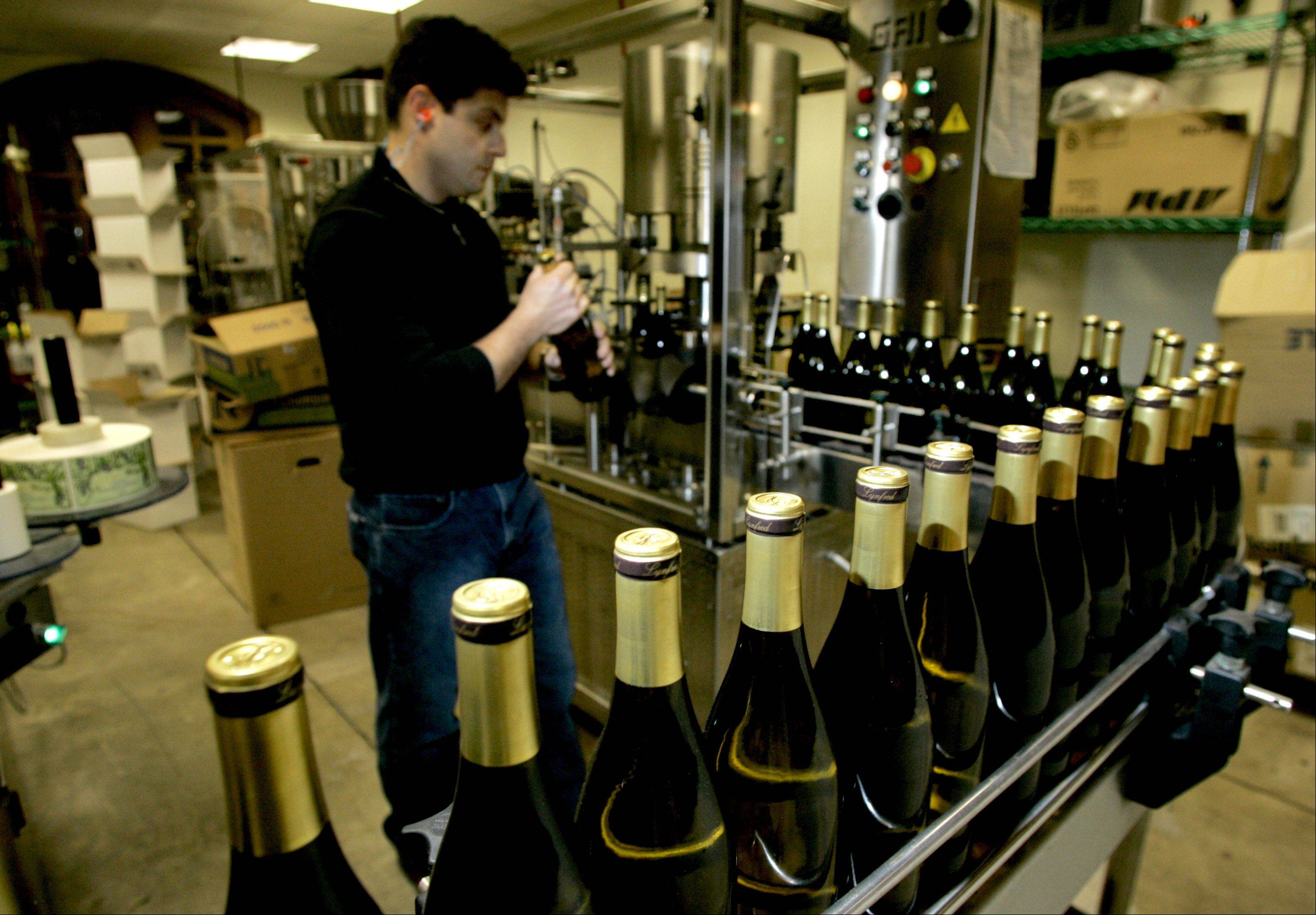 Winemaker Andres Basso oversees bottles of Chardonnay coming off the line to be boxed up at Lynfred Winery in Roselle.