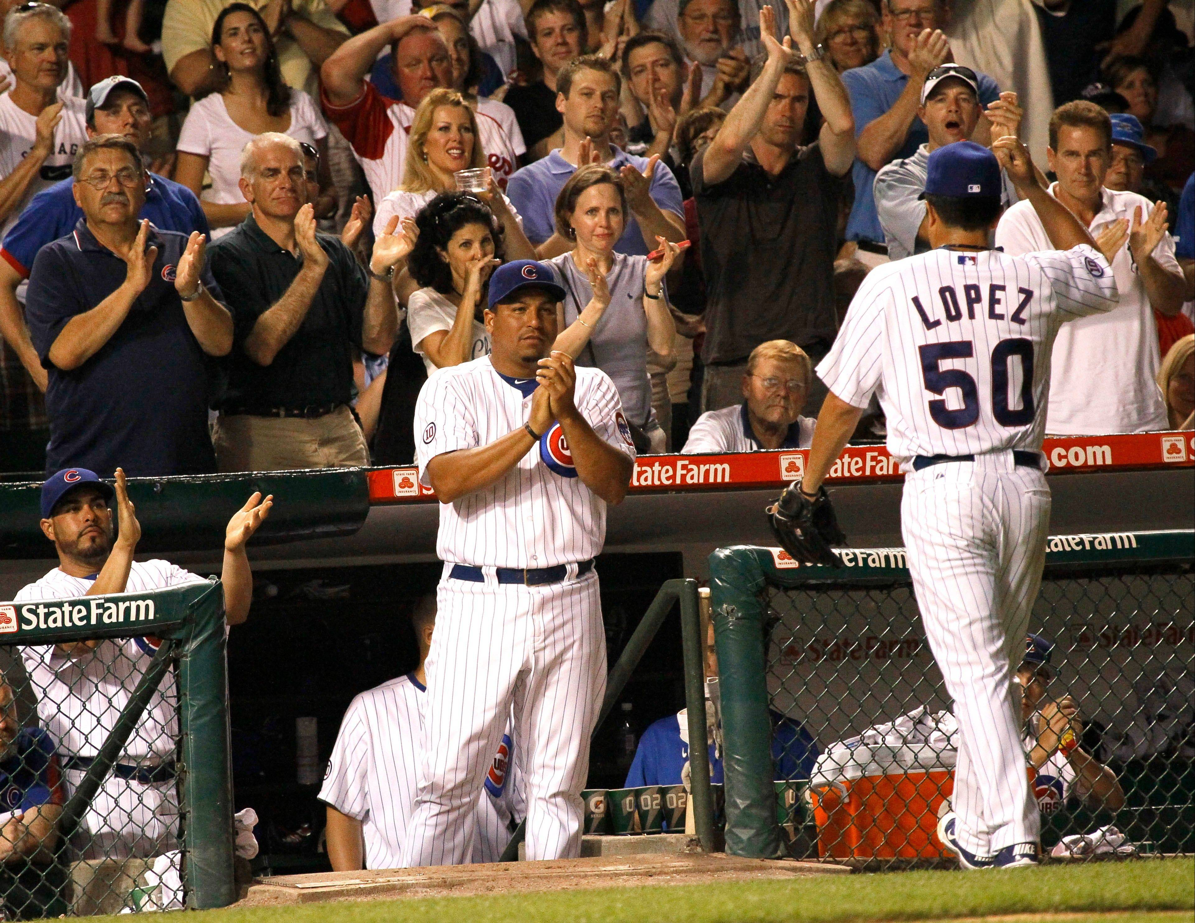 Cubs pitcher Carlos Zambrano, center, leads the applause as starting pitcher Rodrigo Lopez exits the game during the seventh inning Monday against the Phillies at Wrigley Field. Lopez pitched 6⅔ innings, allowing 1 run on 5 hits.