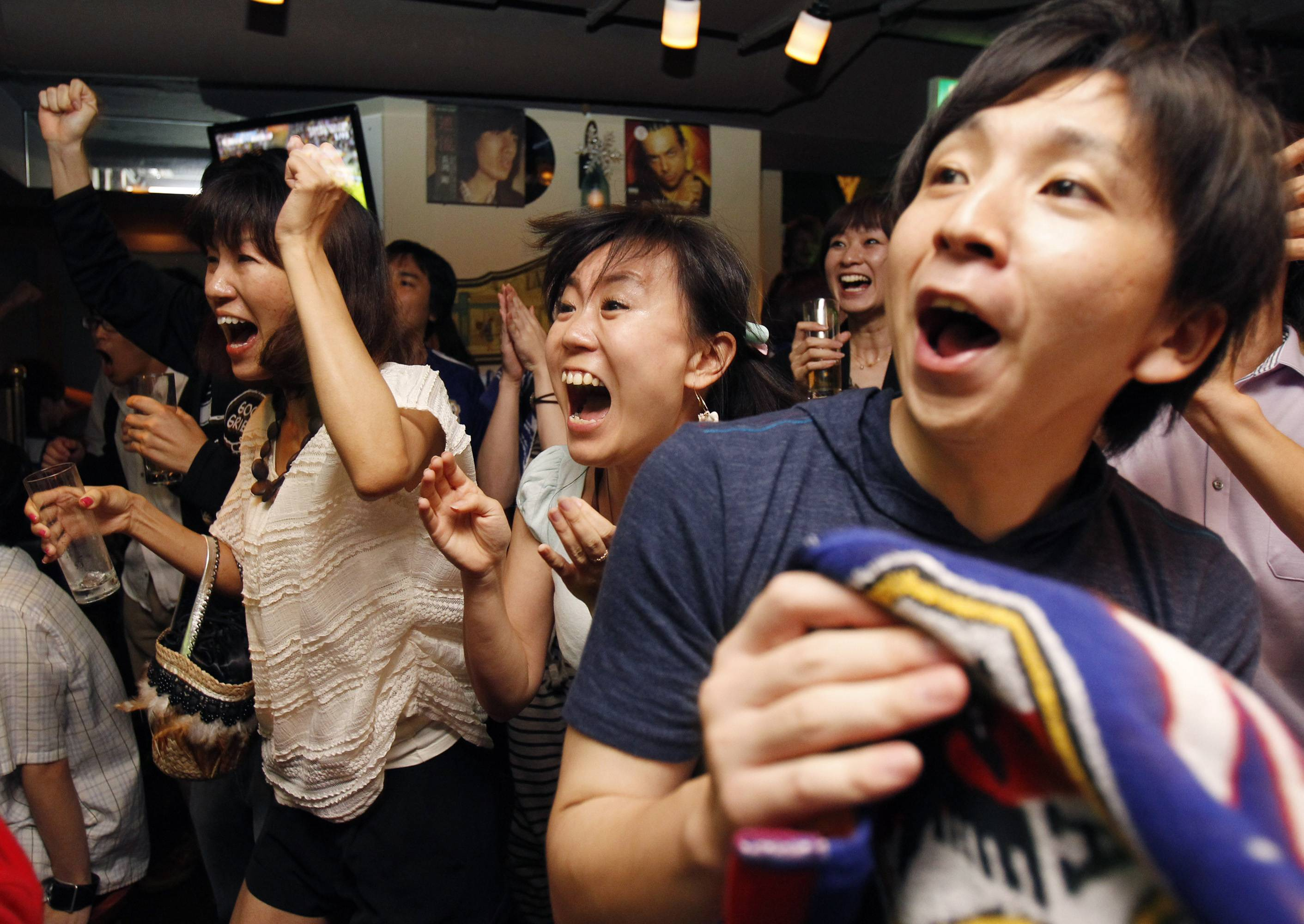 Fans cheer the Japanese team playing with the United States in their Women's Soccer World Cup final match, at the Rooney2008 sports bar in Tokyo. Japan became the first Asian nation to win the Women's World Cup on Sunday.