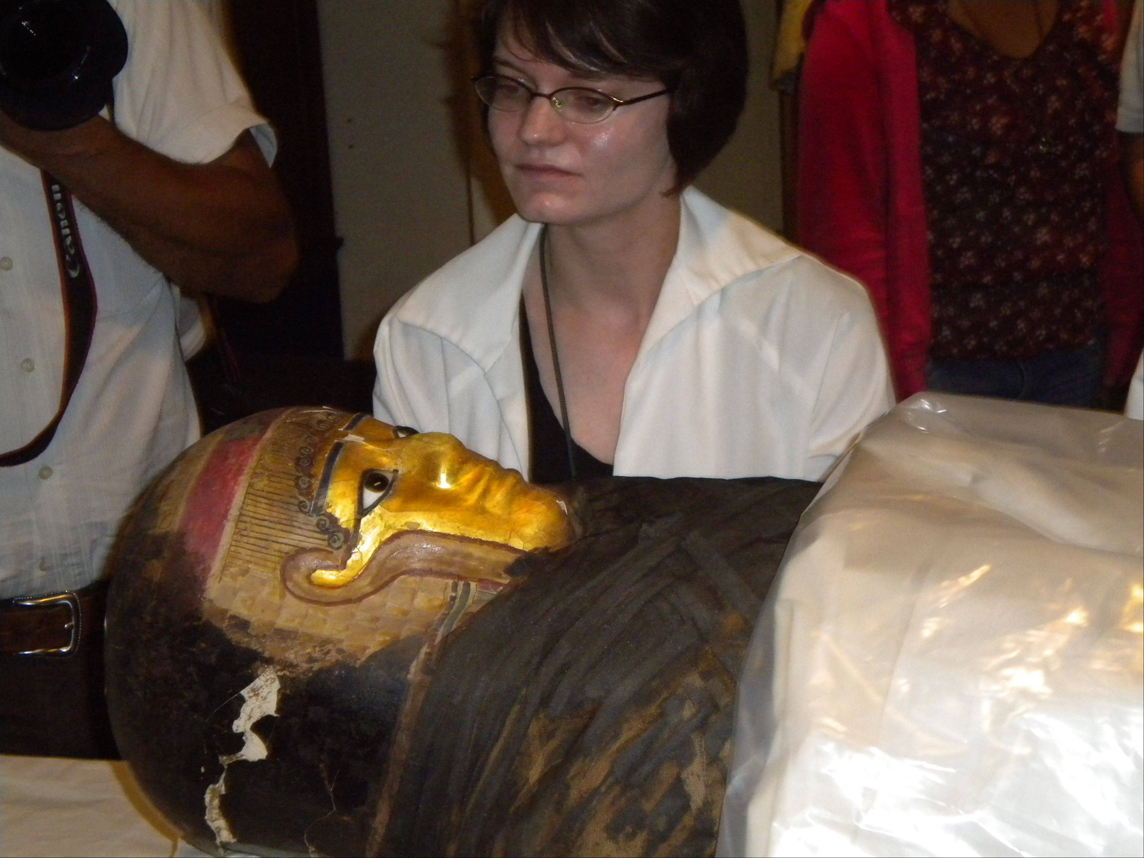 A Field Museum worker helps place a mummy to be scanned by a CT scanner provided by Huntley-based Genesis Medical Imaging Inc.