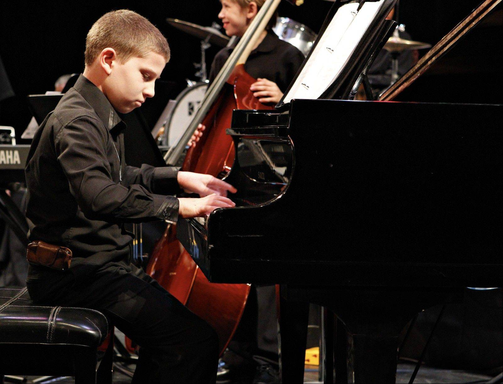 Billy Gensel, 11, warms up before playing with a jazz ensemble. With his severe allergies, the piano surface must be wiped clean with alcohol before he can sit down and play.