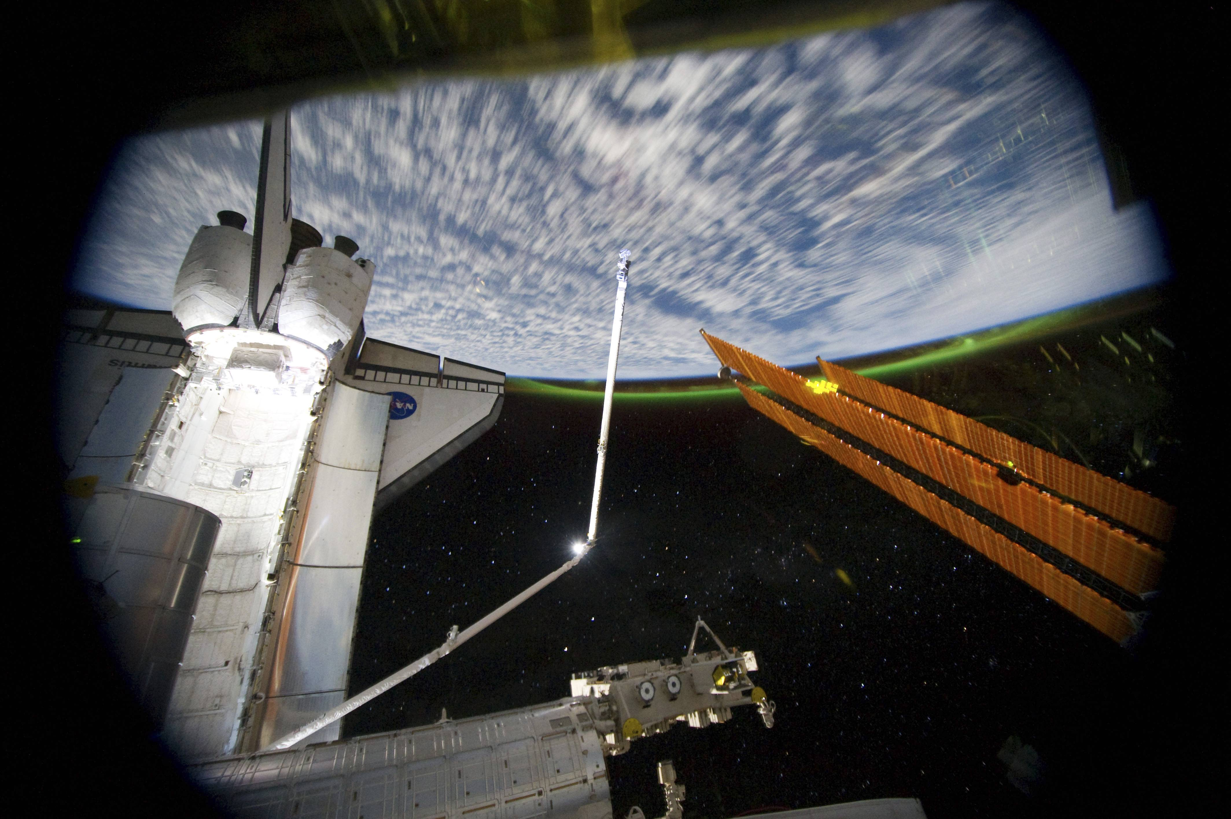 This panoramic view was taken from the International Space Station, looking past the docked space shuttle Atlantis' cargo bay and part of the station including a solar array panel toward Earth. The space shuttle will undock Tuesday for the last time.