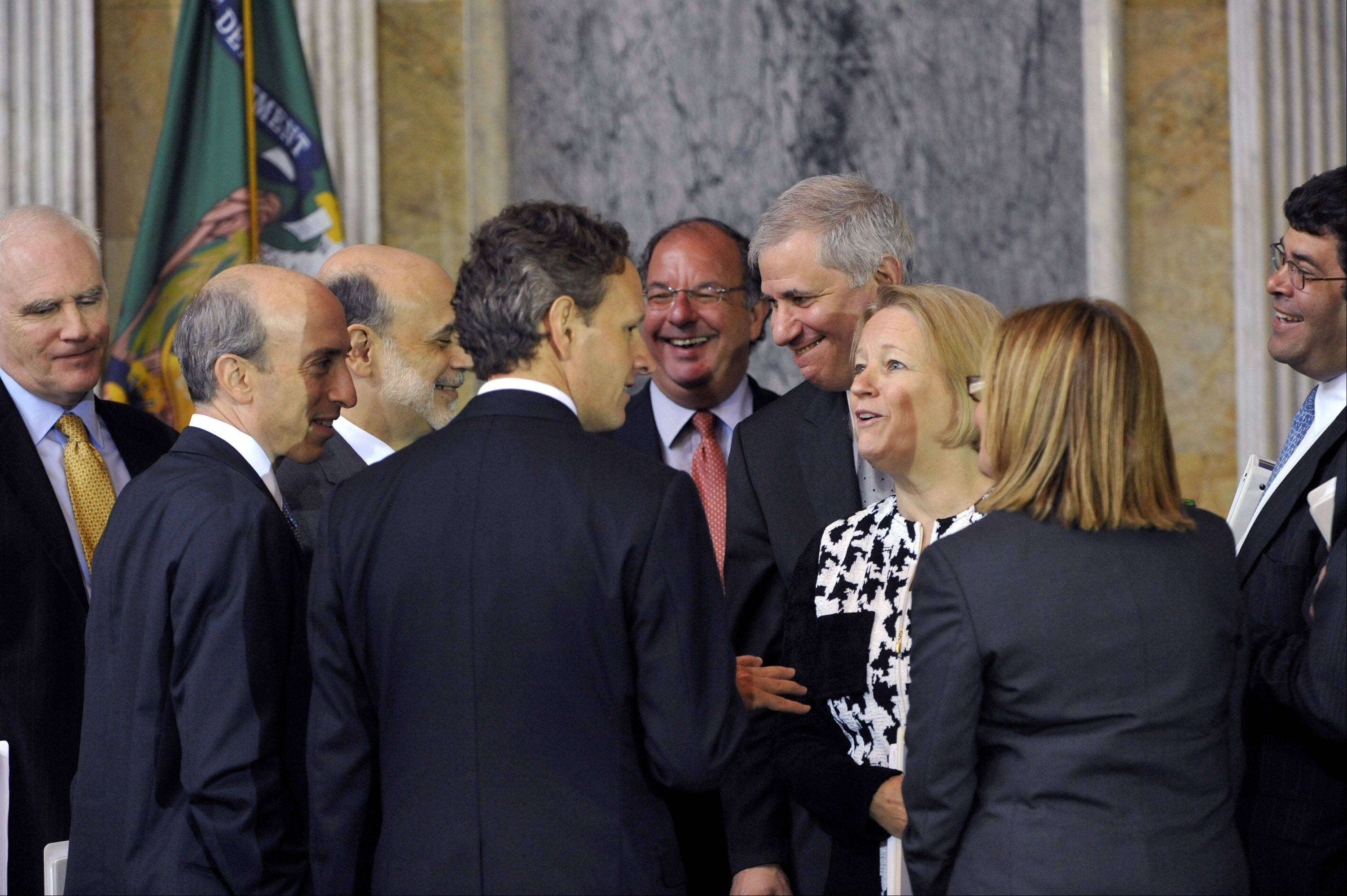 Members of the Financial Stability Oversight Commission talk after meeting in Washington on Monday. That's Treasury Secretary Timothy Geithner, center with his back turned, and Federal Reserve Chairman Ben Bernanke, to his left.