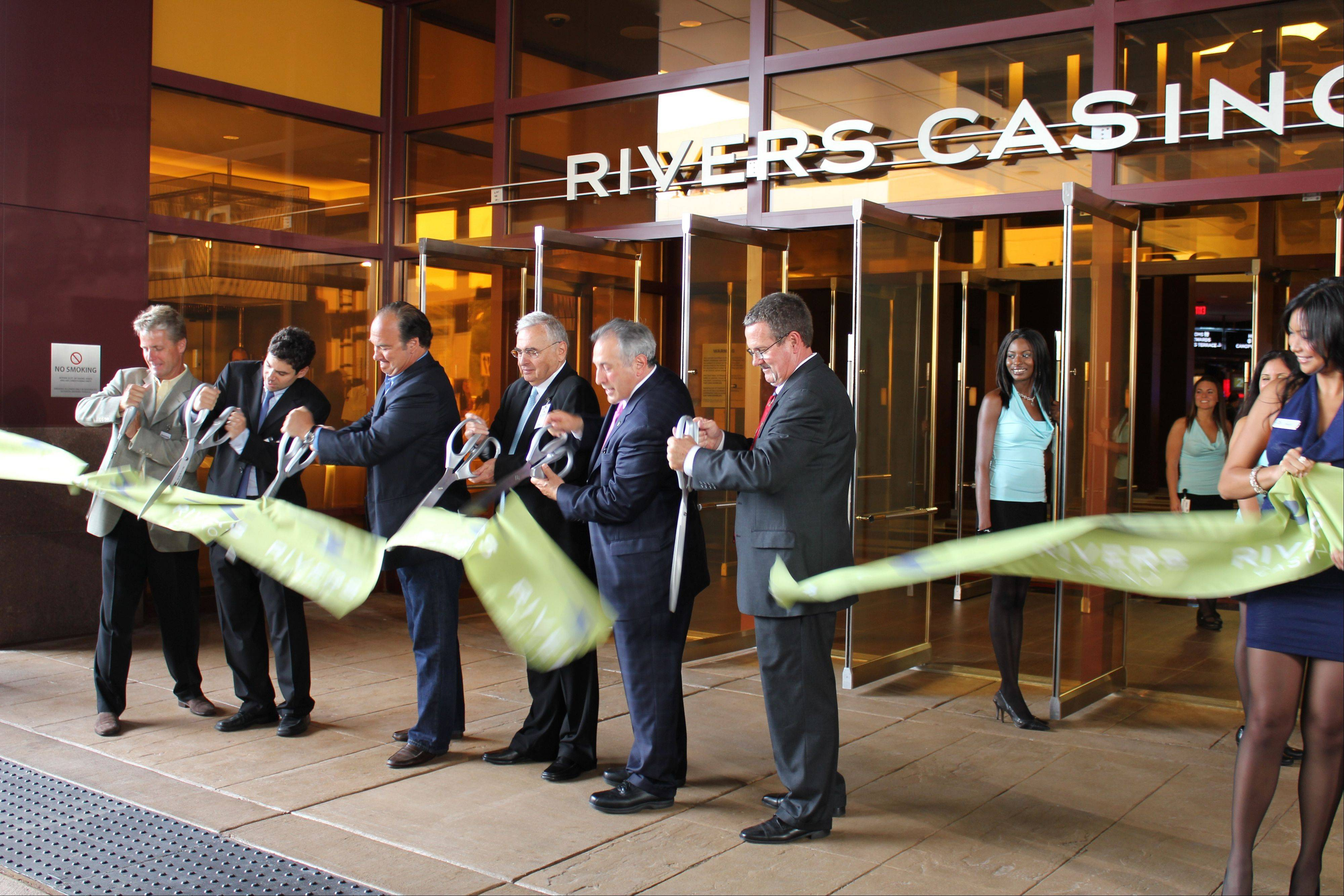 Des Plaines officials, actor Jim Belushi, third from left, casino owner Neil Bluhm, fourth from left, and other dignitaries cut a ceremonial ribbon at today's grand opening of the Rivers Casino.