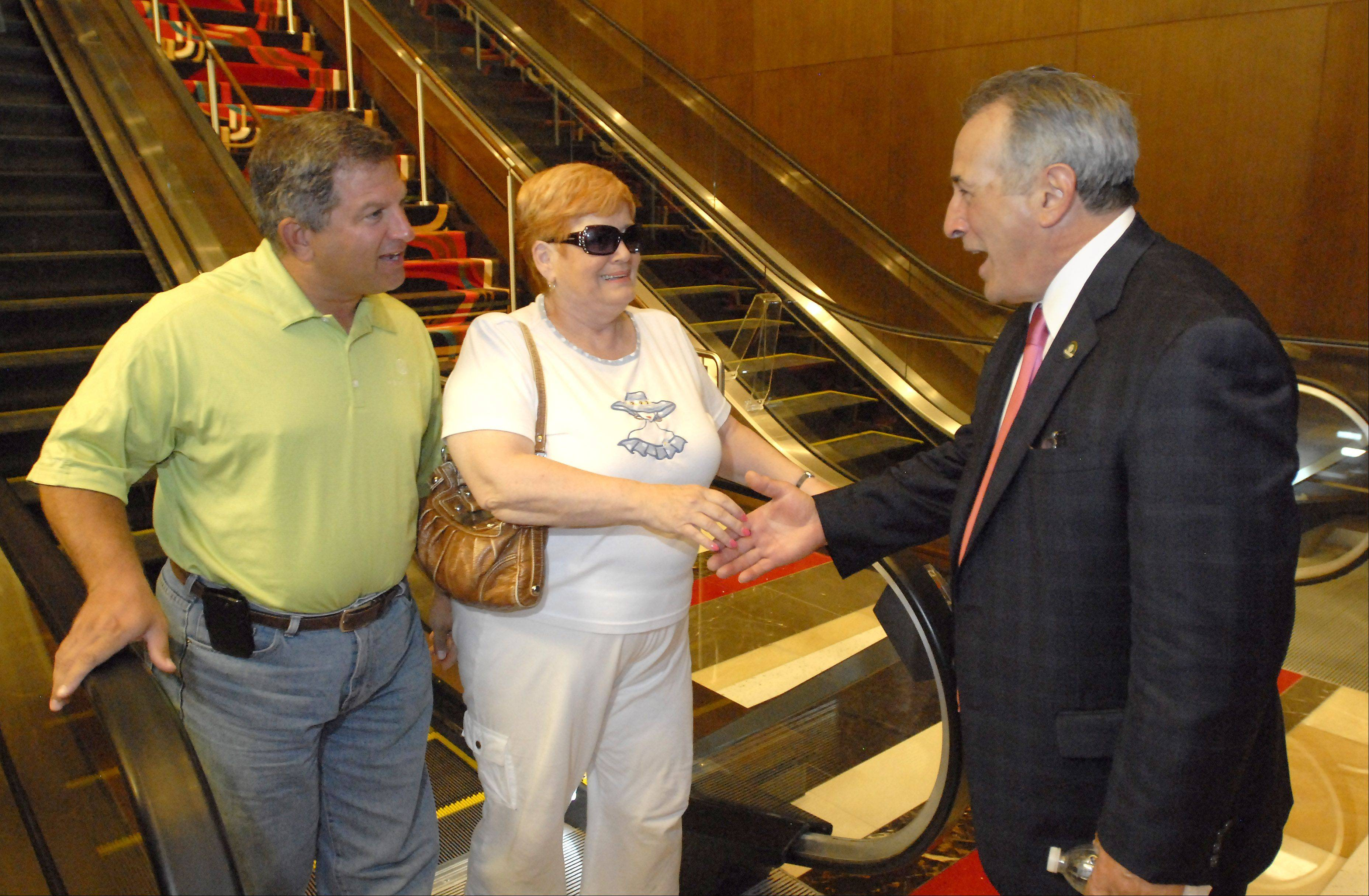 Des Plaines Mayor Marty Moylan greets gamblers Scott Rose of Lindenhurst and Fran Derkowitz of Philadelphia during the grand opening of the Rivers Casino Monday.