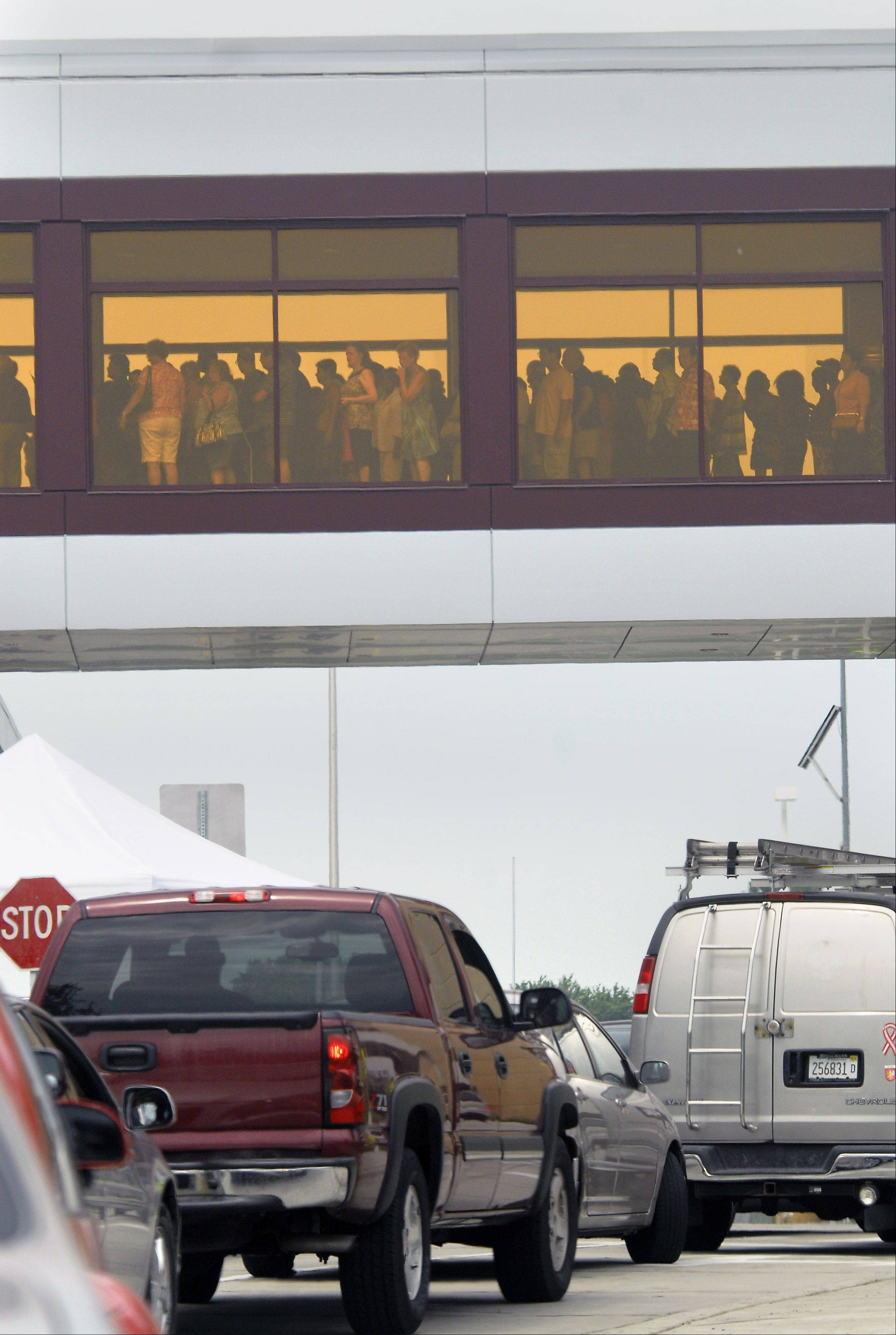 People cross the skybridge from the parking garage as motorists are turned away because it was at capacity on opening day of the Rivers Casino Monday in Des Plaines.