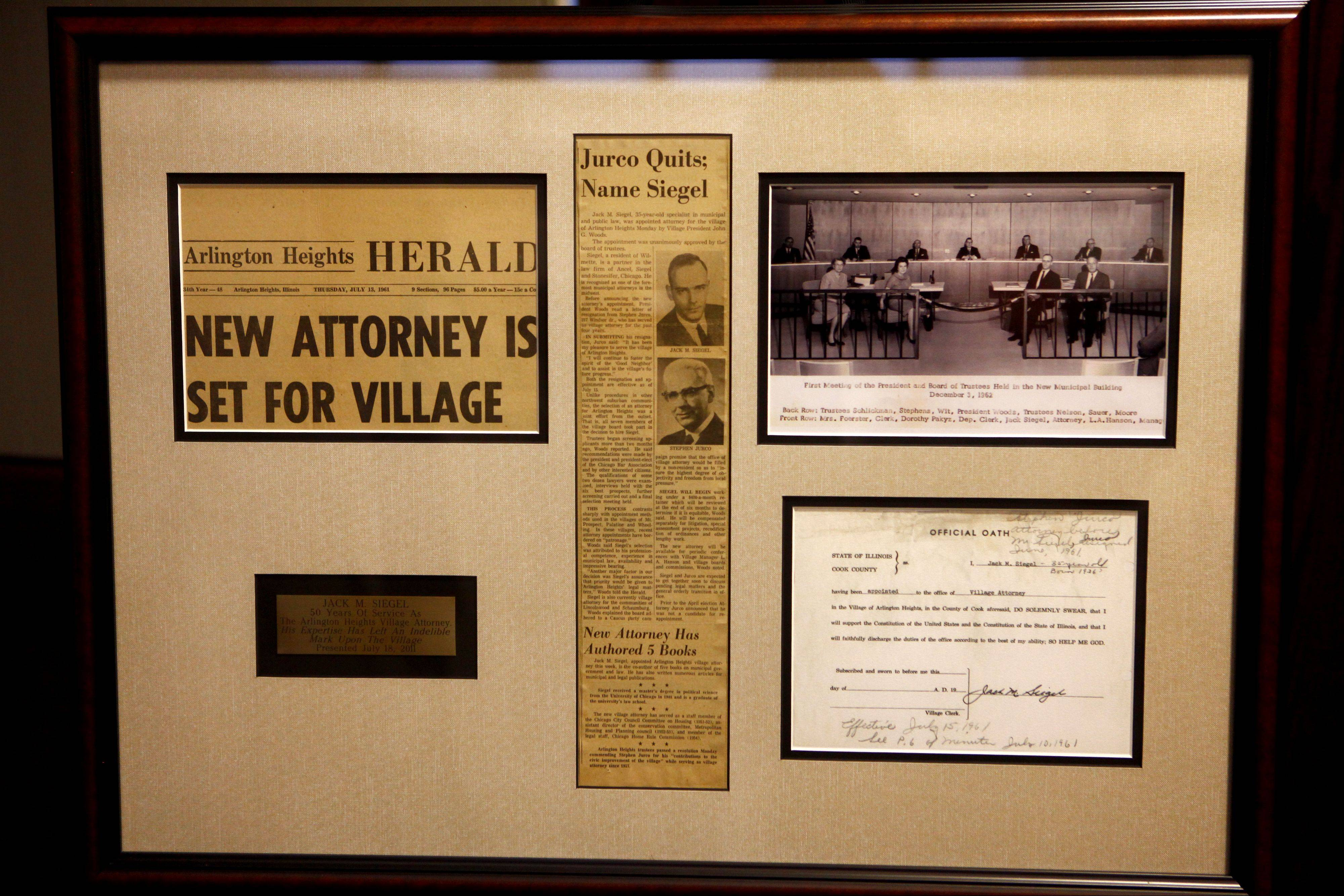 Mementos given to Jack Siegel for 50 years as village attorney include a Herald article announcing his appointment and a photograph of the first Village Board meeting in what was then the new village hall.