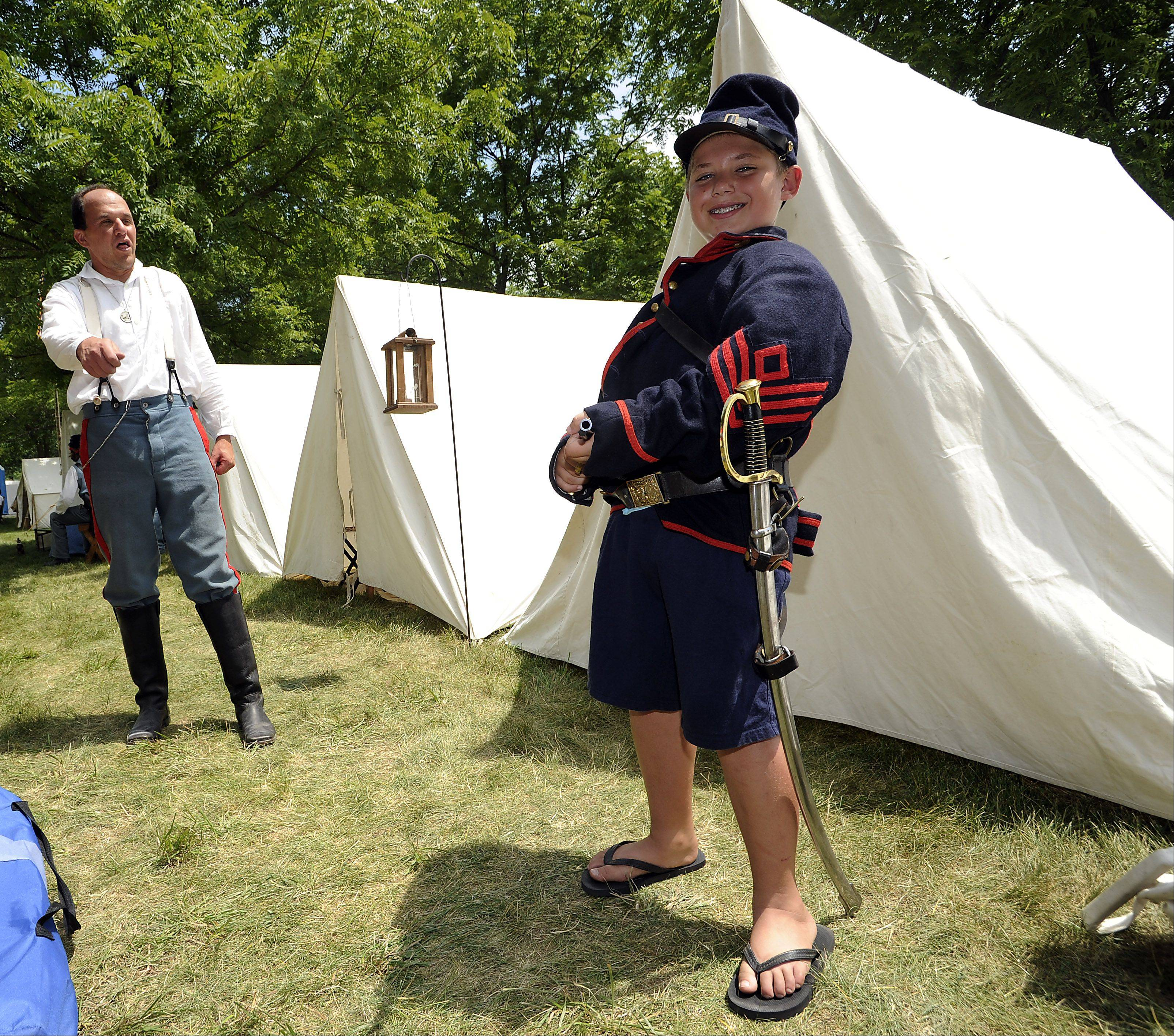 Elk Grove Village's Mike Gregory dresses up Eric Socha,11, of Itasca letting him experience first hand how hot and heavy the wool uniforms are on a hot summer day during the first day at the 20th annual Civil War days in the Lake County Forest Preserve on Saturday.