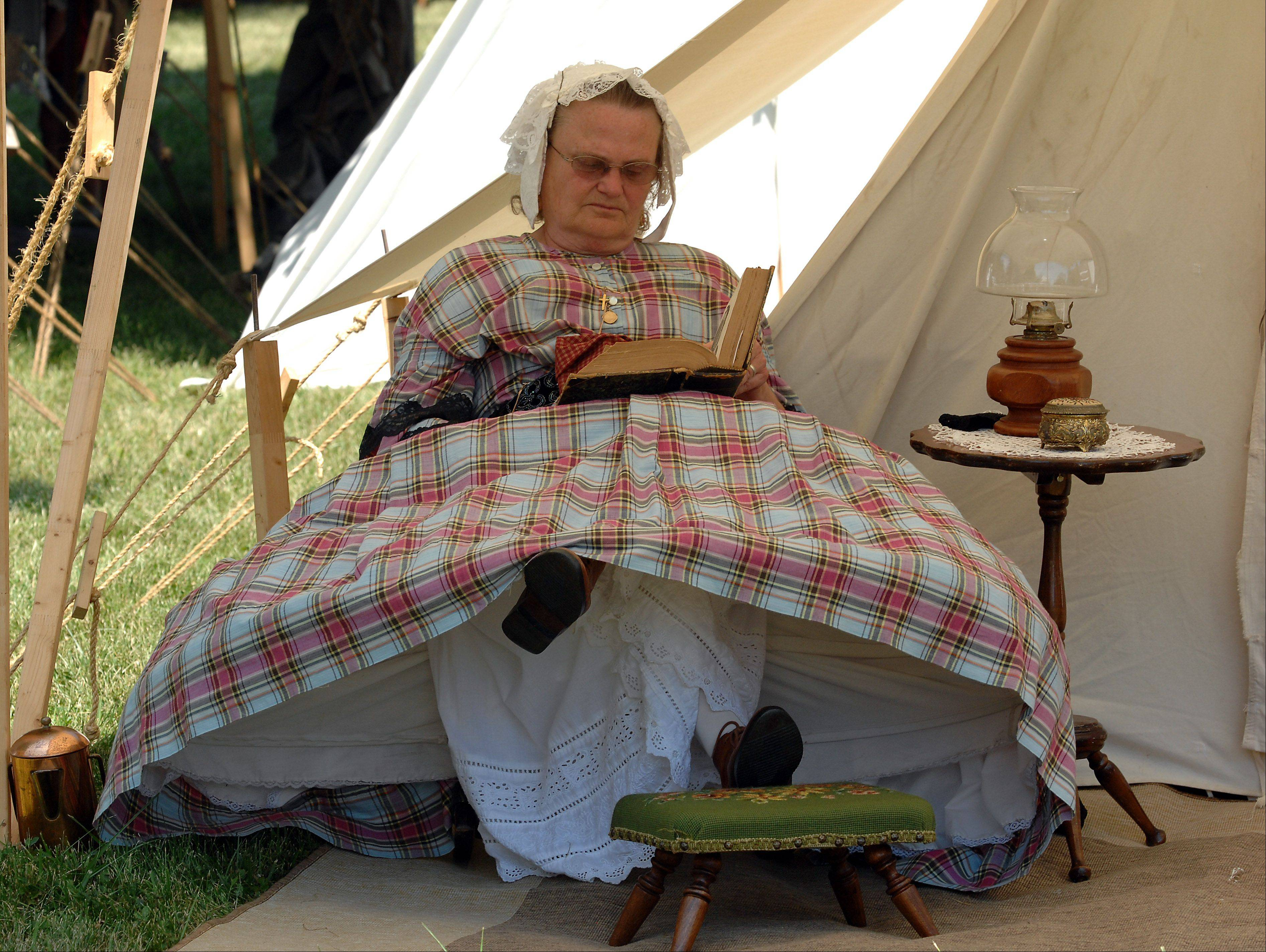 Ruth Jankiewicz of Wisconsin sits reading her 1862 Lady's Book on a hot summer day as the men head off to battle on the first day at the 20th annual Civil War days in the Lake County Forest Preserve on Saturday.