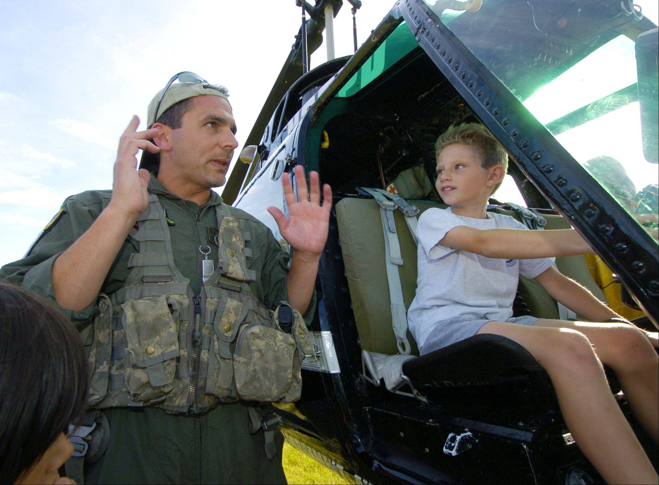 Seated in a helicopter, Timothy Knoop, 8, of Hanover Park talks with Dan O'Shea, an Elgin Police Department sergeant and a senior tactical flight officer with the Law Enforcement Aviation Coalition during the Hanover Park Police Department annual COPS Day picnic at East Harbor Park Wednesday.
