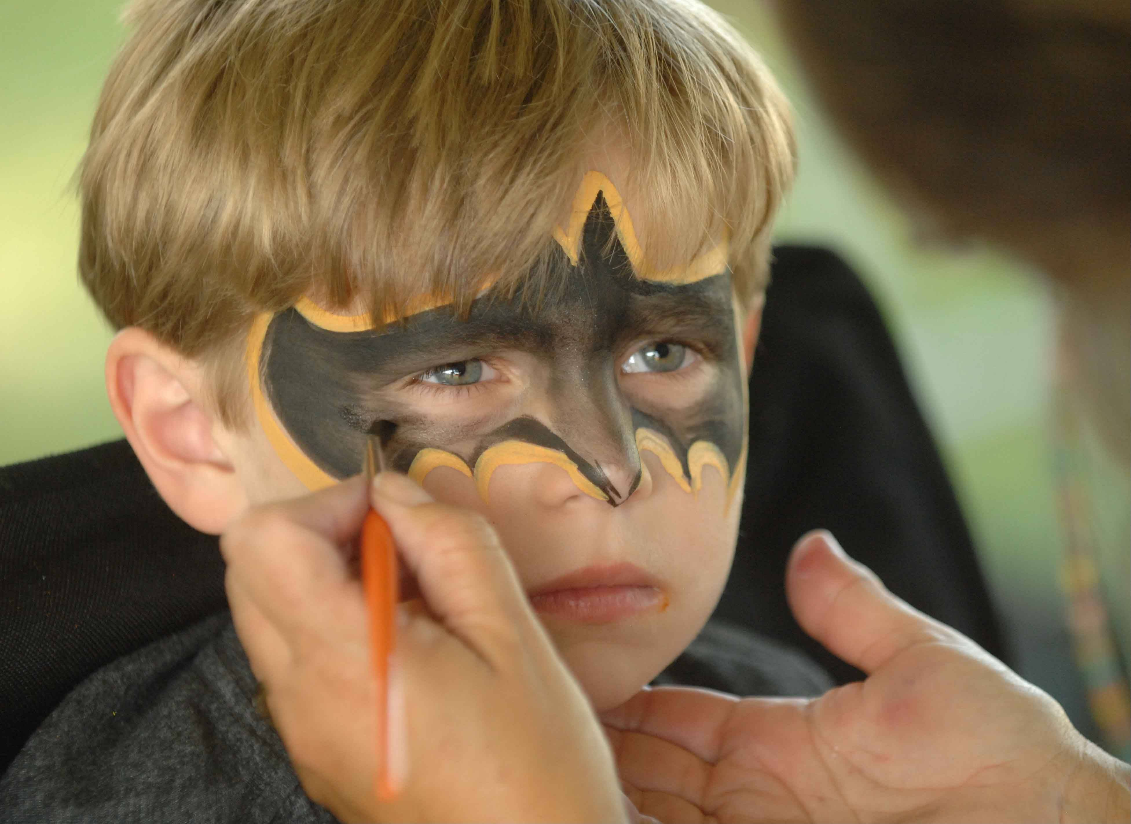 Dominic Esposito,4, of Itasca, gets a Batman-style mini makeover during Itasca Fest at Washington Park Thursday. The fest runs through the weekend and offers fun and games for all ages.