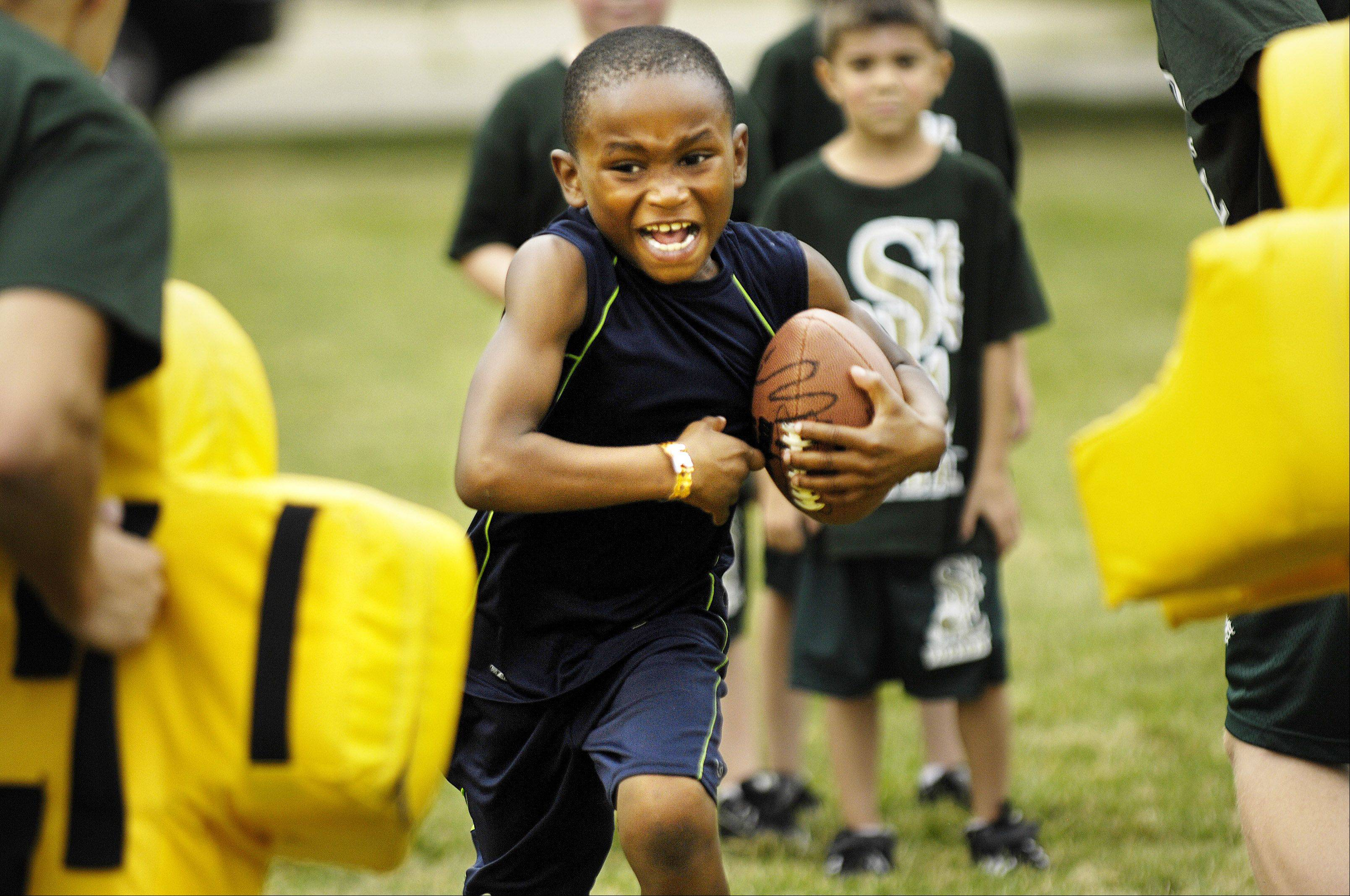 Seven-year-old Jordan Nubin shows no fear as he charges through the defense at a St. Edward Catholic High School football camp for youth Thursday at Abbott Field in Elgin. First through eighth graders were coached through drills by the high school coaching staff and the football team players.