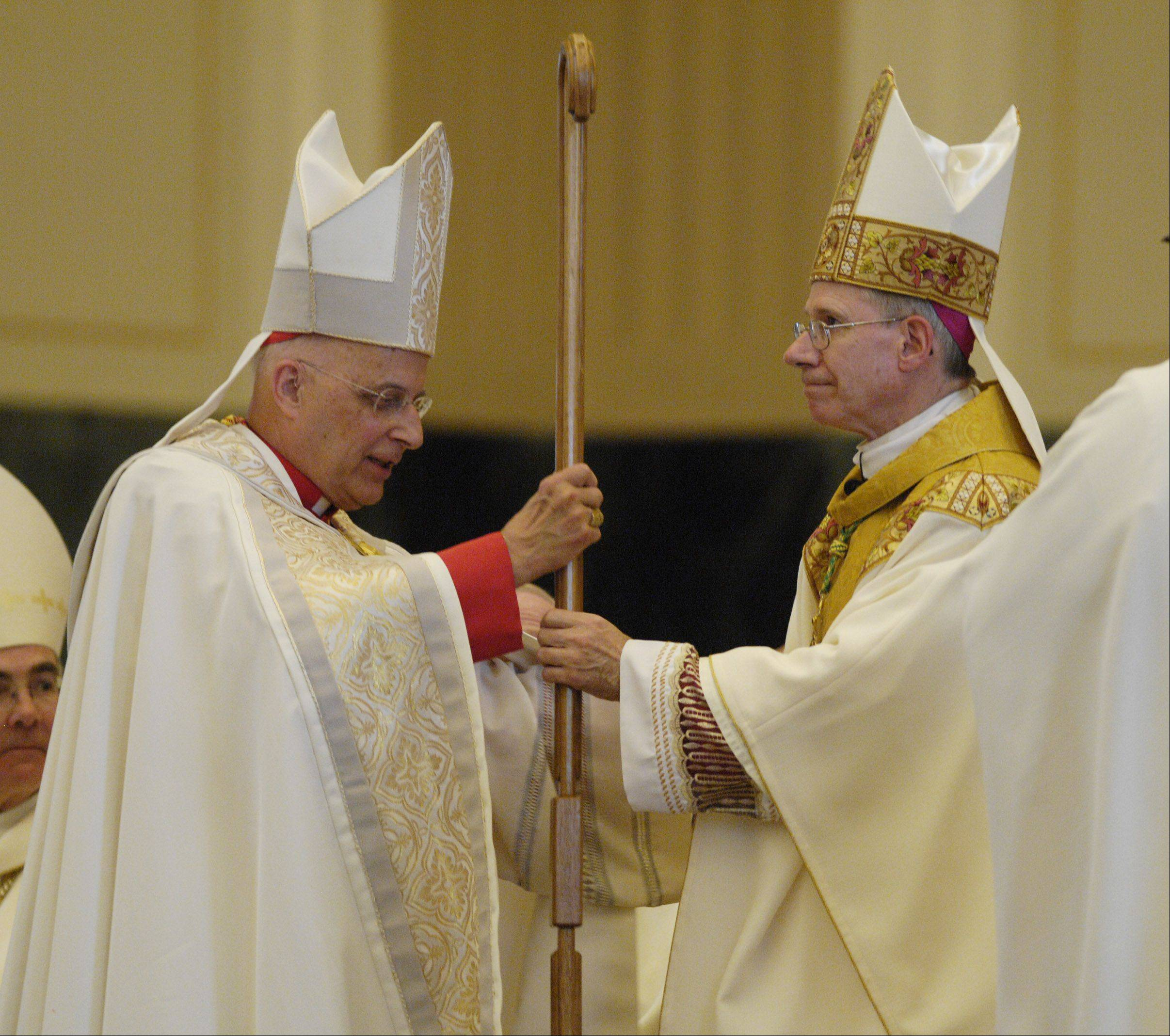 Francis Cardinal George of the Chicago Archdiocese passes the crosier to Rev. R. Daniel Conlon, during his installation as the fifth bishop of the Diocese of Joliet. The installation took place at the Cathedral of St. Raymond in Joliet.