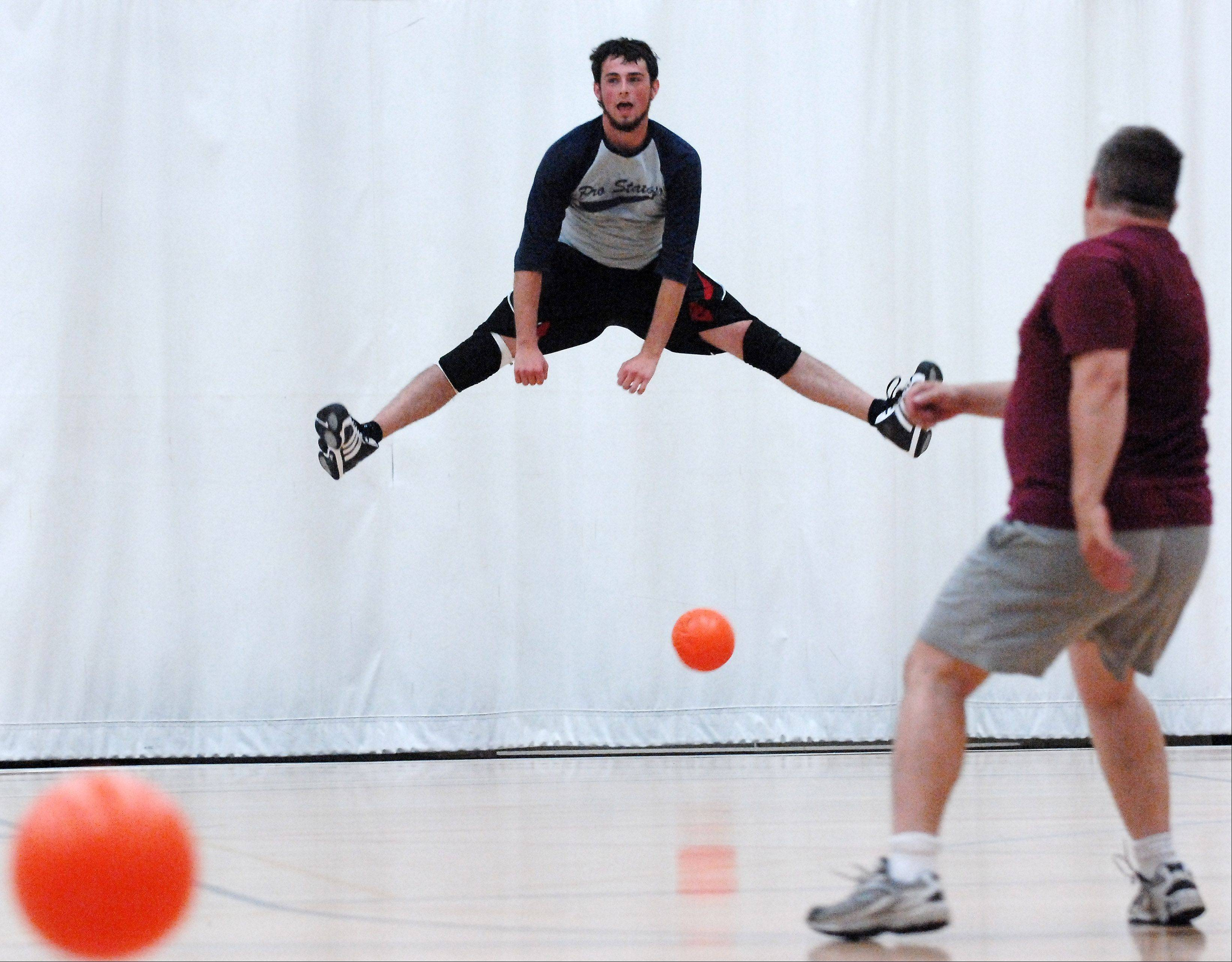 "Devin McManus, 20, of Roselle jumps to avoid a throw by Todd Hartwell of Elgin as members of the ""Hammertime"" team practice at Christ Community Church in St. Charles Friday for this weekend's annual championship tournament of the National Amateur Dodgeball Association."
