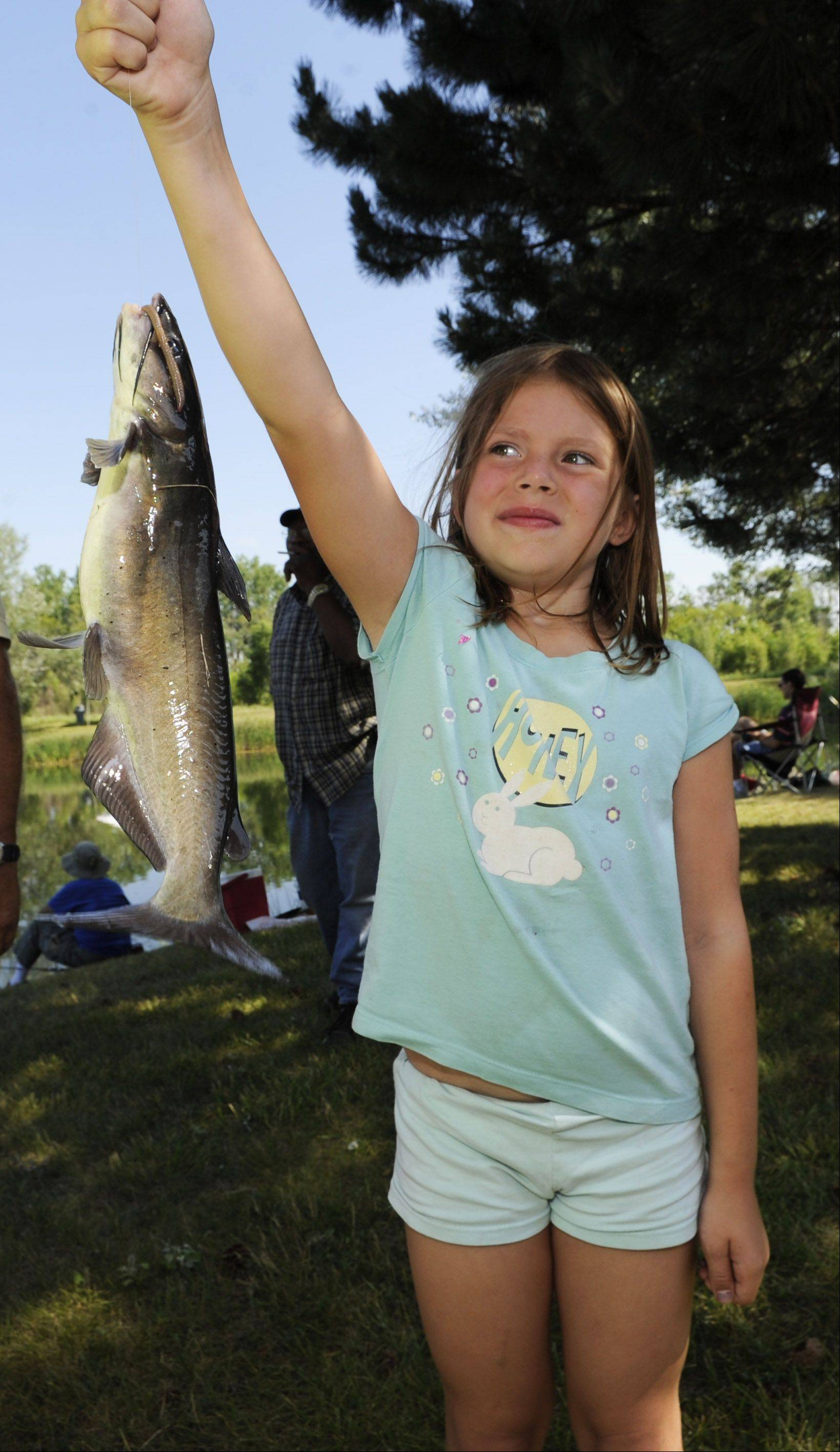 Proud of her catch but also a little scared of it, Savannah Wilson,7, of Island Lake holds the whopper of the day, a worm-caught 1-pound 16 inches long catfish at the Mundelein Police Department annual Bobbers fishing derby on Saturday.
