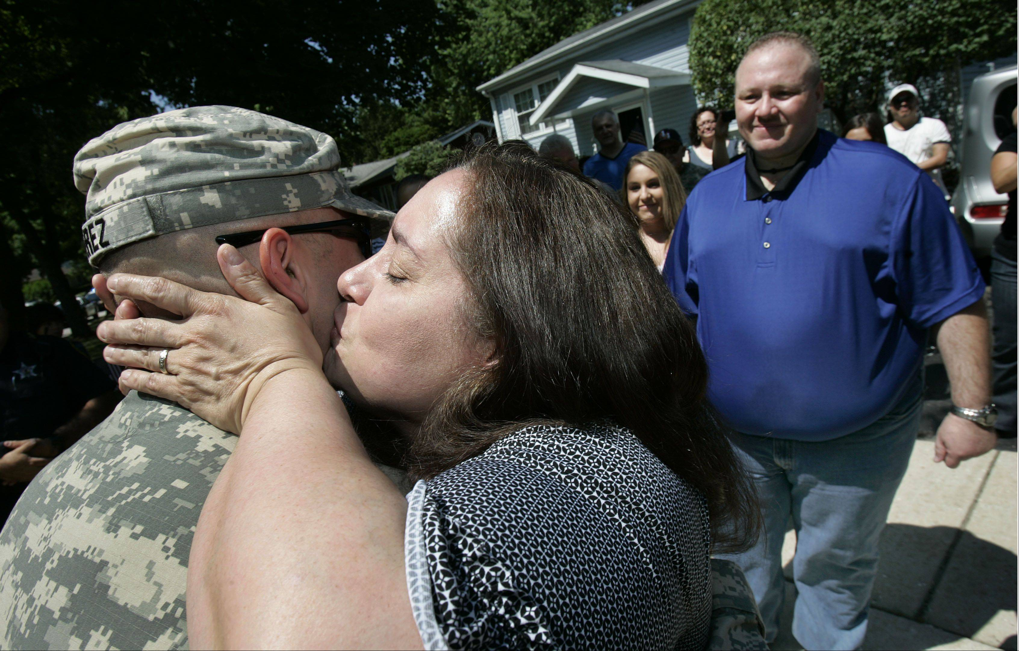 "Margie Perez gives her 23-year-old son U.S. Army PFC Andrew Perez a kiss after returning home from active duty in Iraq Friday morning in Vernon Hills. Vernon Hills officials, police officers and Countryside Fire officials welcomed home Perez through the village's ""Operation Welcome Home"" initiative. He is serving with the U.S. Army 3-7 Infantry Battalion and was stationed at Al Asad Air Base in Iraq. Perez will be home for 18 days, then he will go to Ft. Stewart in Georgia. His father, Efrain is on the right."