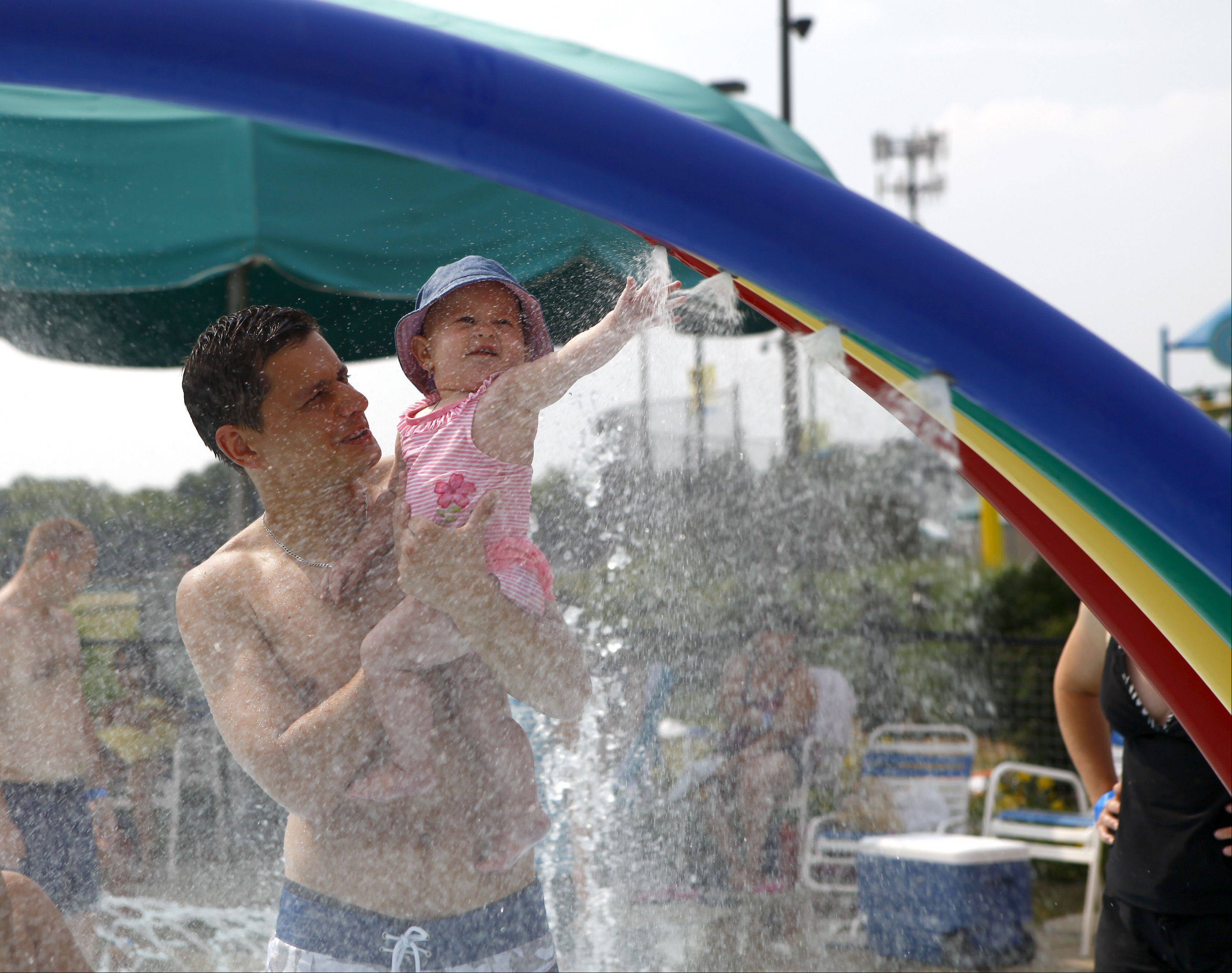Arthur Panek, from Des Plaines, plays with his daughter Maya, 10 months, in one of the many water features at Rainbow Falls Water Park on Sunday.