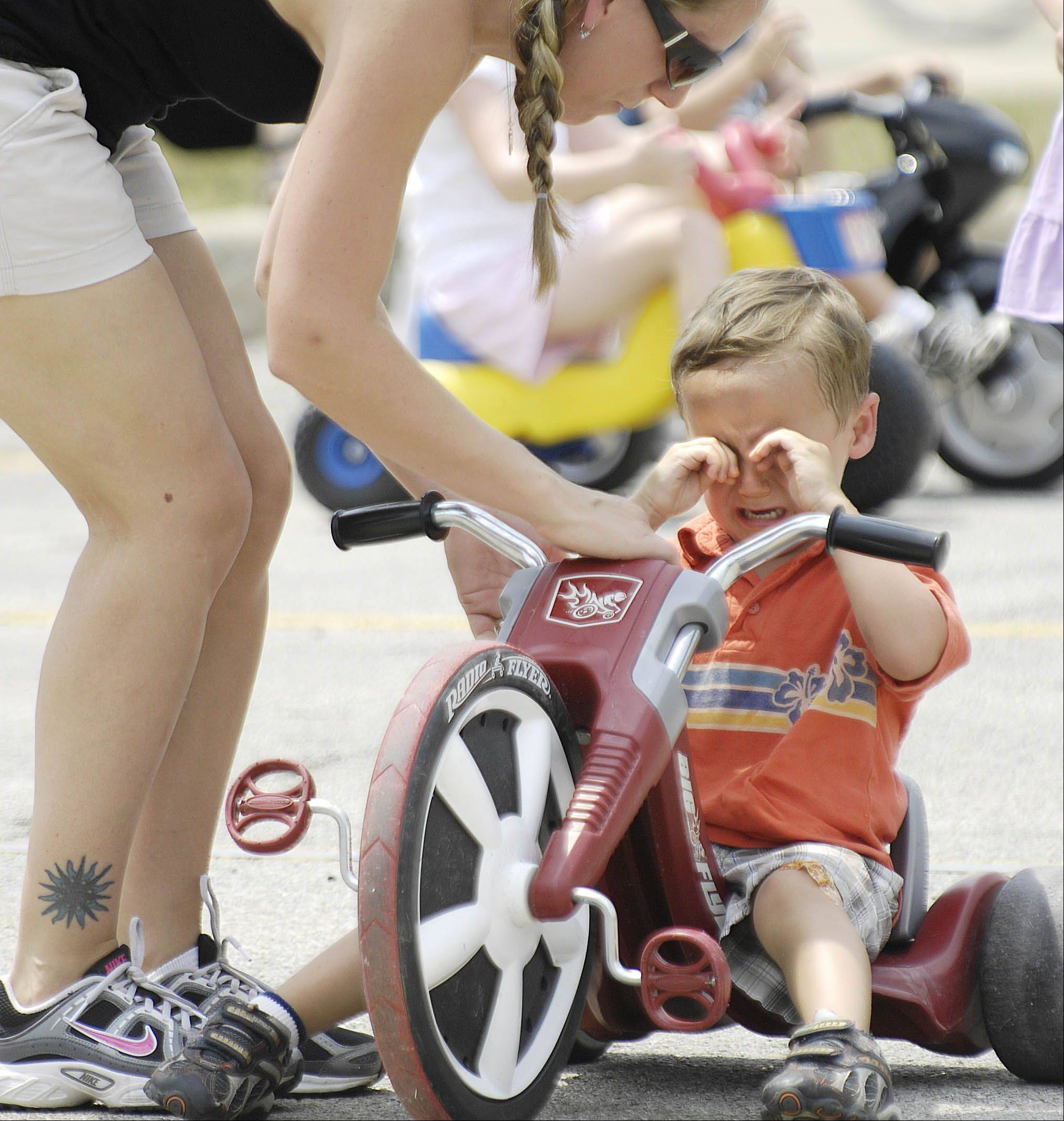 Kyle Vogtmann, 4, reacts at the finish line when he realizes he did not win a trophy in the Lil 500 Big Wheel Race at the Batavia Windmill City Festival Sunday. His mom Colleen promised ice cream anyway.