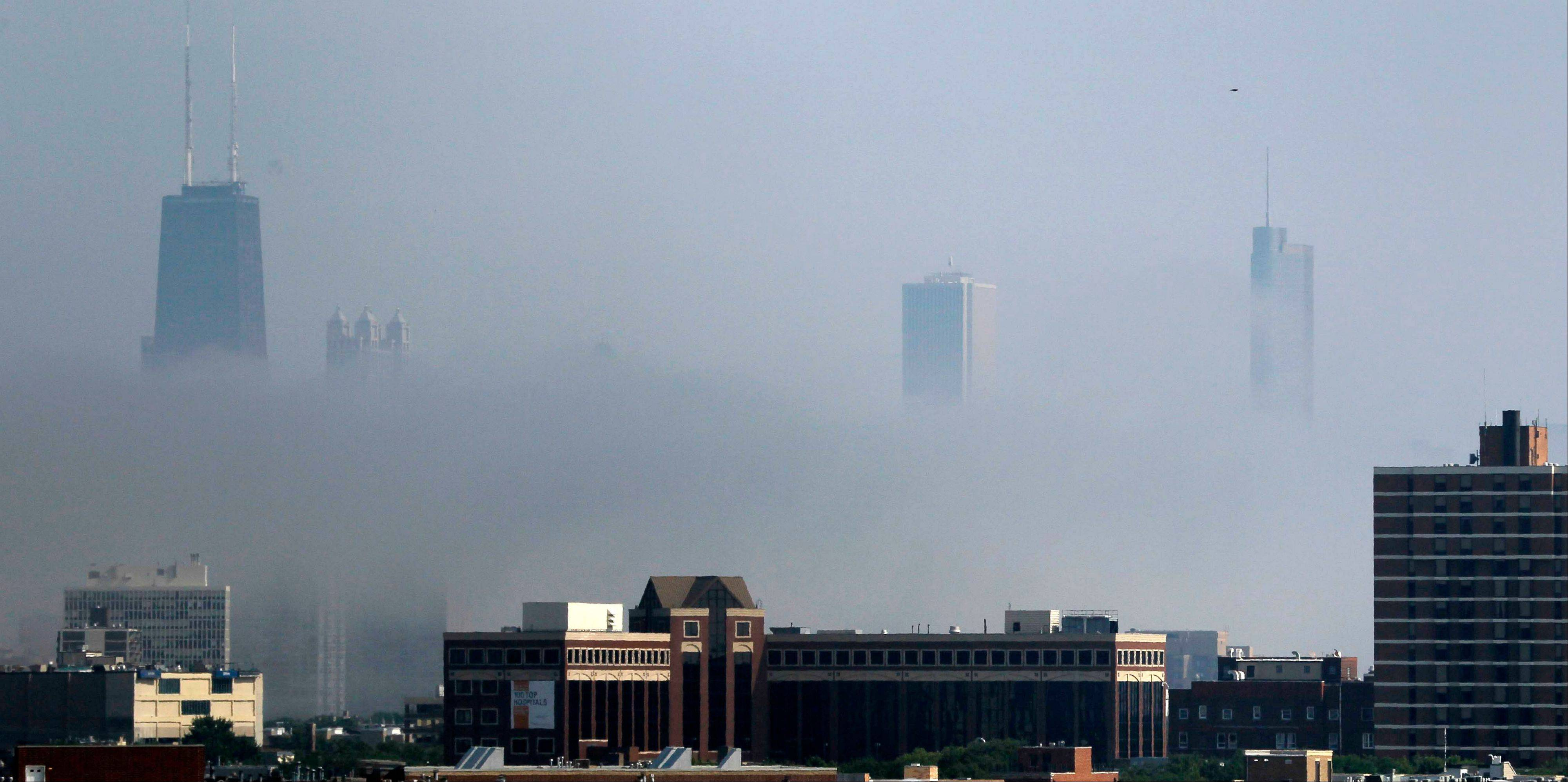 Cool air off Lake Michigan filters through as fog in downtown Chicago on Tuesday.