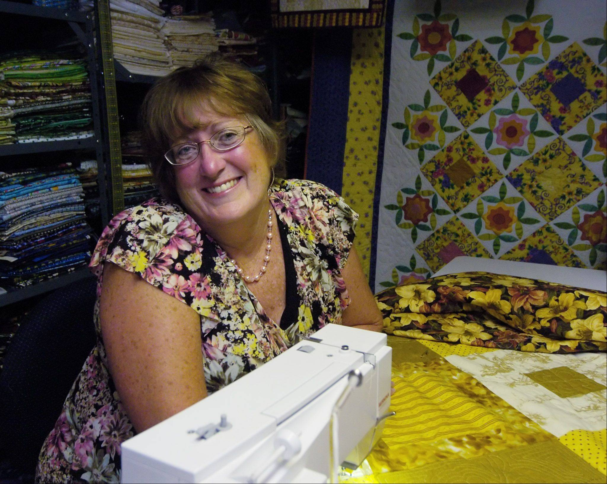 Jane Underys, with a sampling of the more than 200 quilts she has made at her Arlington Heights home.