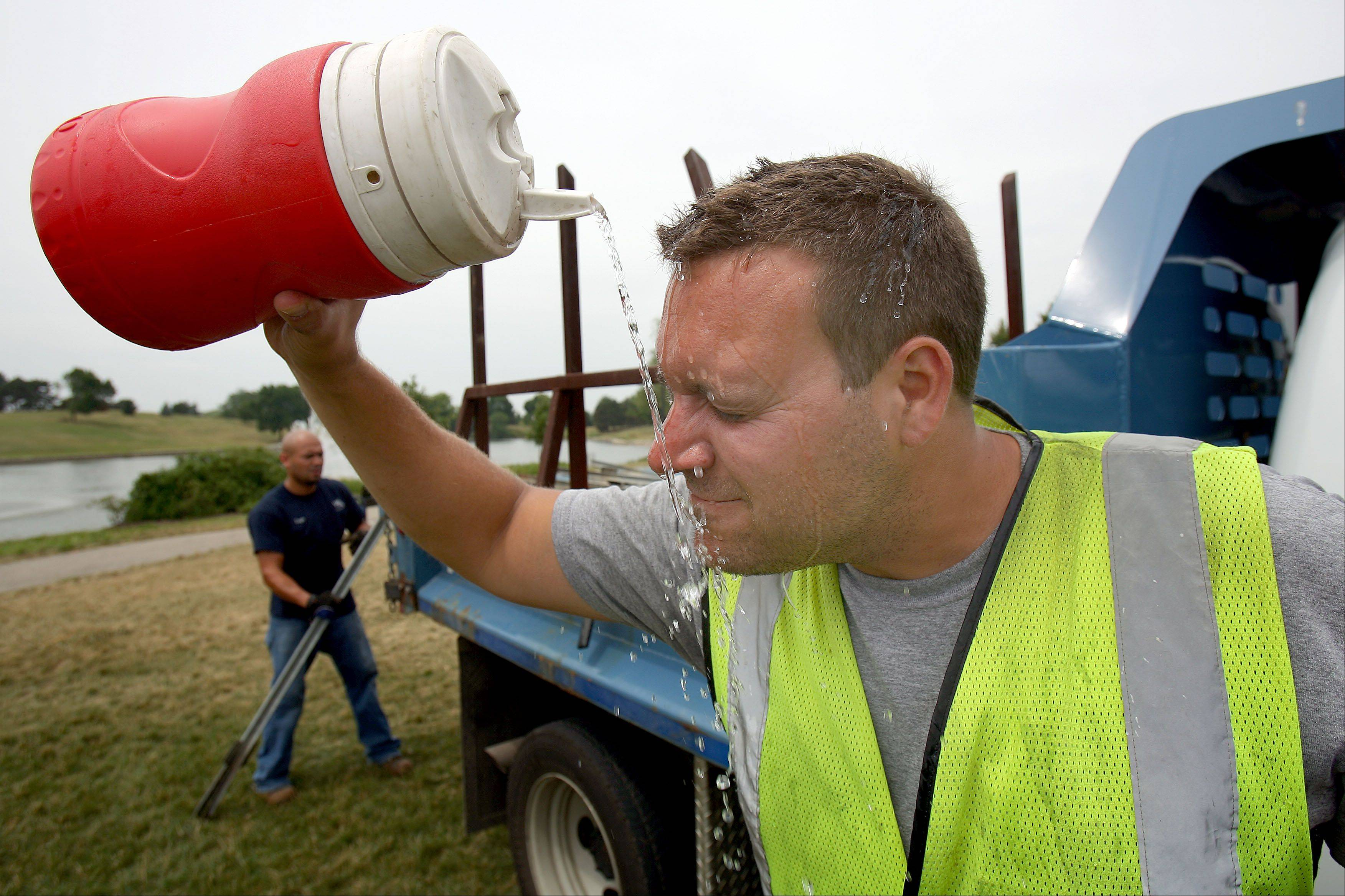 Vernon Hills Public Works worker Ryan Papak, right, beats the heat by dousing himself with water as he and his co-worker Sergio Soto, left, work to remove posting from Century Park following Vernon Hills summer Celebration Monday.