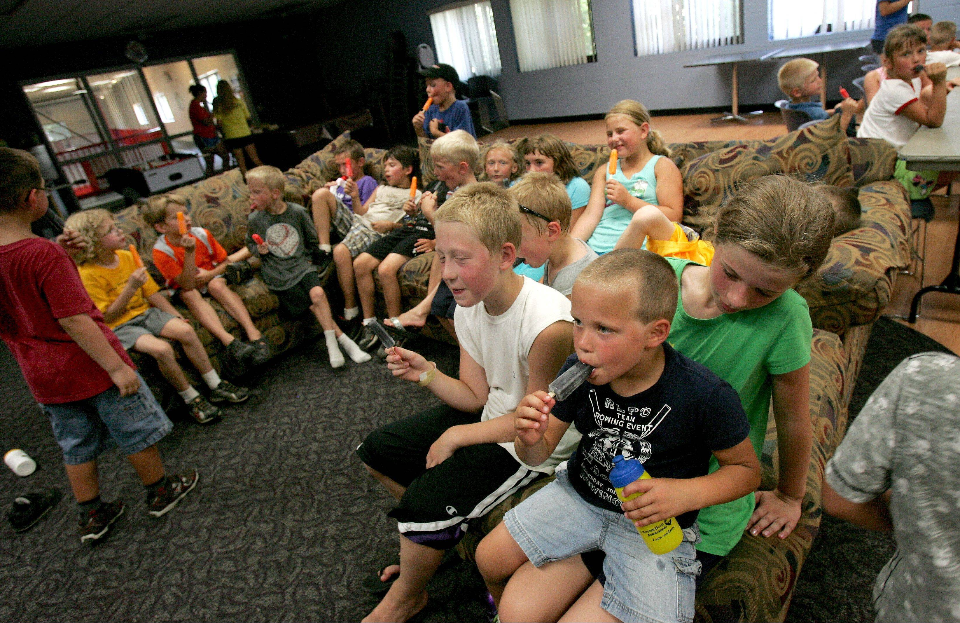 Kids from the Camp Adventure and Camp Butterflies at the Itasca Recreation Center take a Popsicle break inside Tuesday.