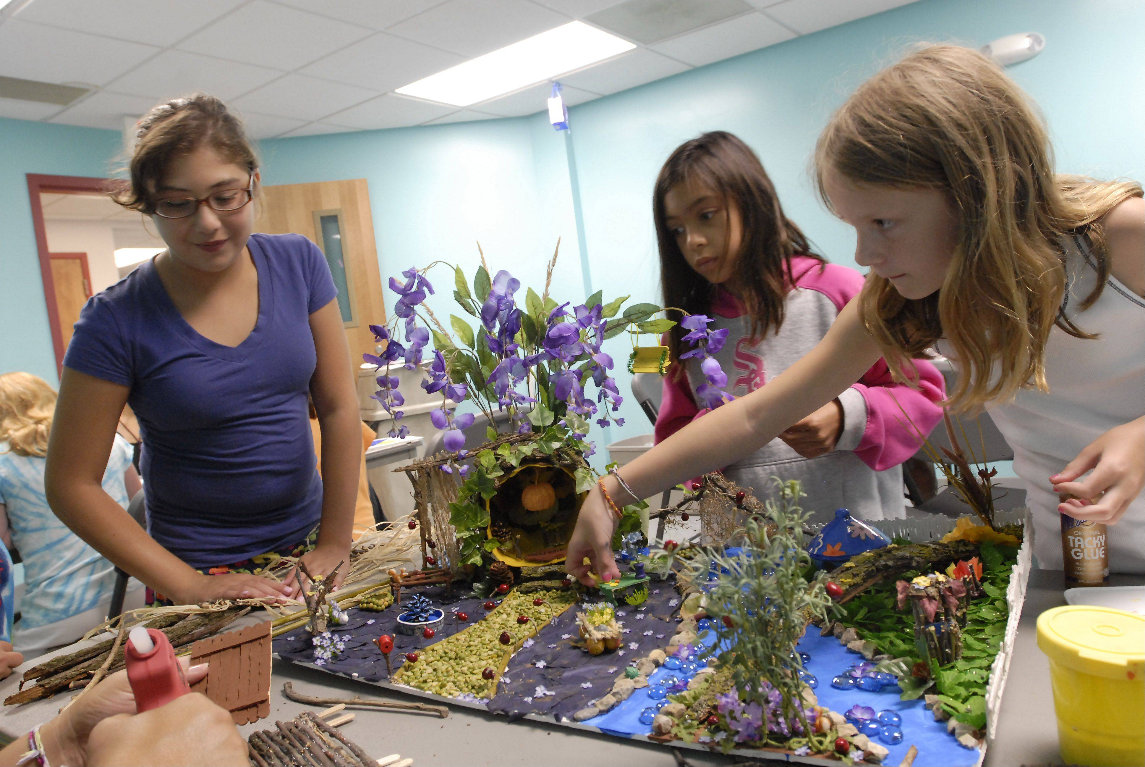 Tara Gabriel, 11, Morgan Grelyak, 8, and Lindsay Cohen, 7, all of Schaumburg, work on a fairy house in the craft room at the Schaumburg Park District Day Camp as the heat wave continues in the area Tuesday afternoon.