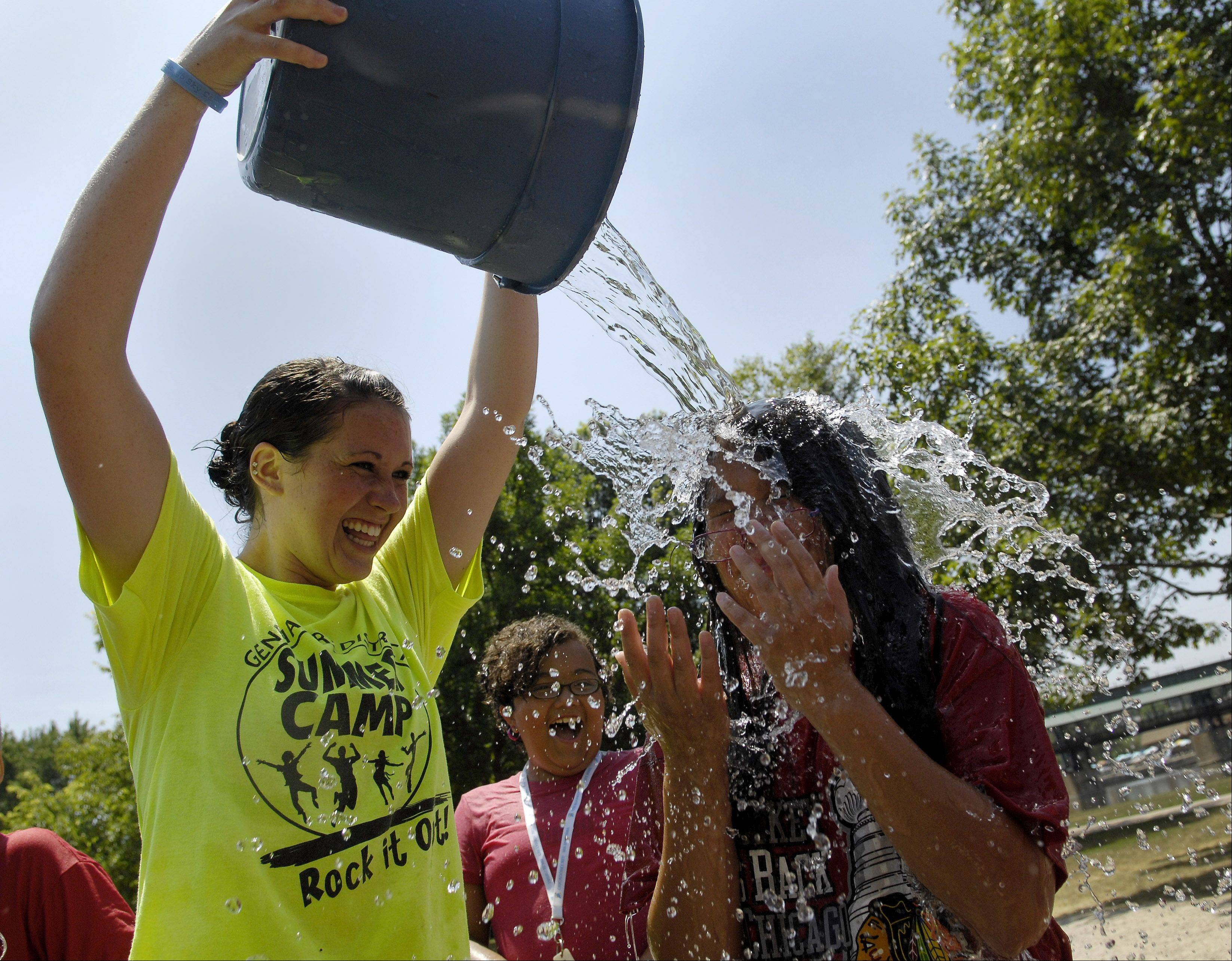 "Camp counselor Karli Sayner dumps a bucket of water on Emma Ramirez, 9, of Batavia as kids from the Geneva Park District's ""Adventure Camp"" cool off at Pottawatomie Park in St. Charles Tuesday."