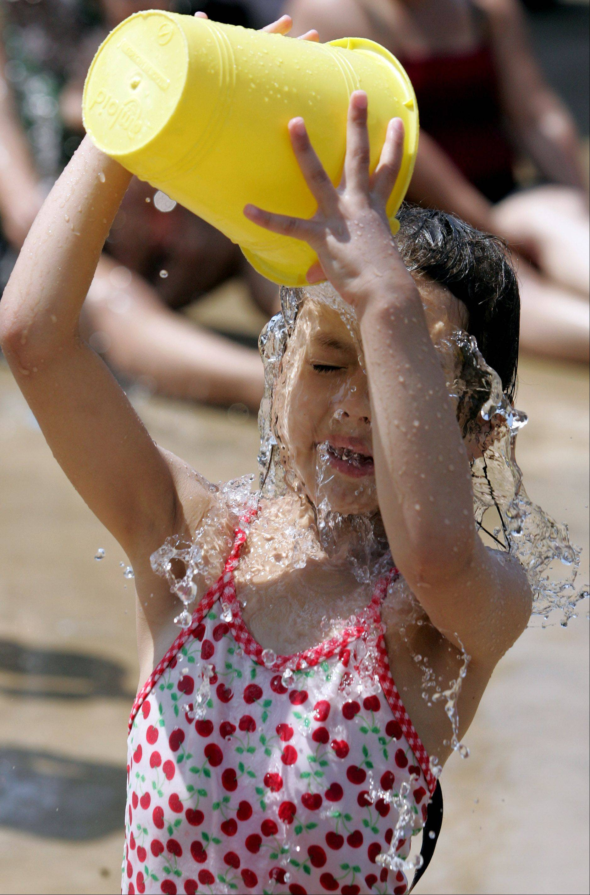 Jennifer Valois, 6, of Villa Park, pours a bucket of water over herself as she cools off with her family at the Water Spray Park in Lombard on Tuesday.