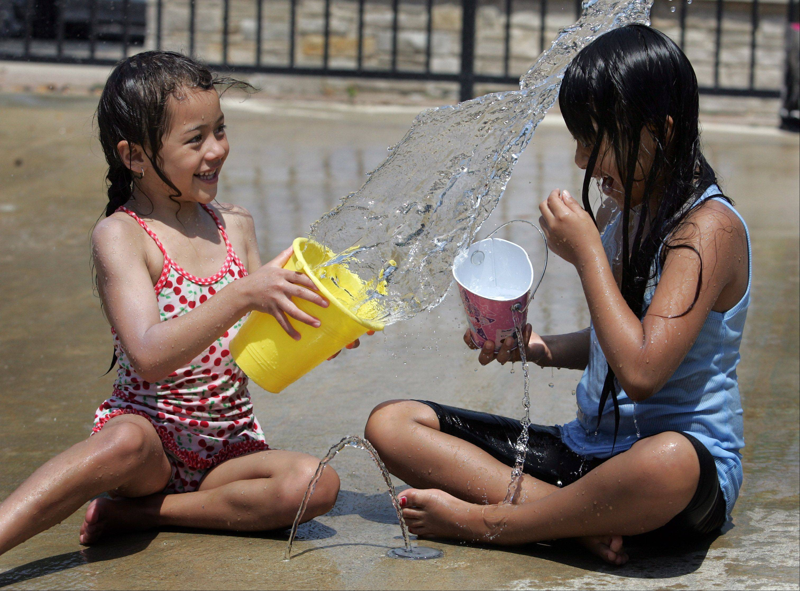 Jennifer Valois, 6, left, splashes Jessica Valois, 8, with water. The cousins, both of Villa Park, were cooling off in Tuesday's heat at the Water Spray Park in Lombard.