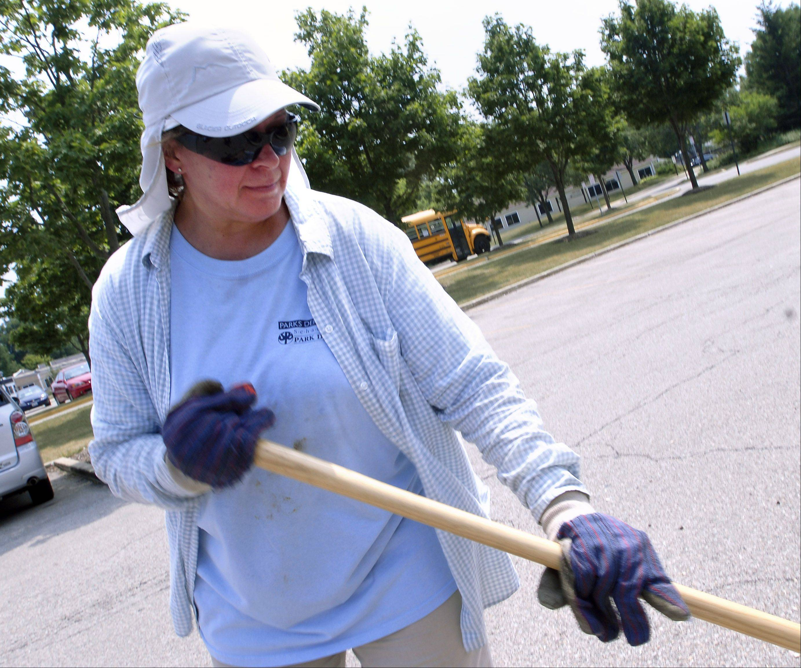 Schaumburg Park District employee Maria Puga carries on with her task of raking on Tuesday afternoon.