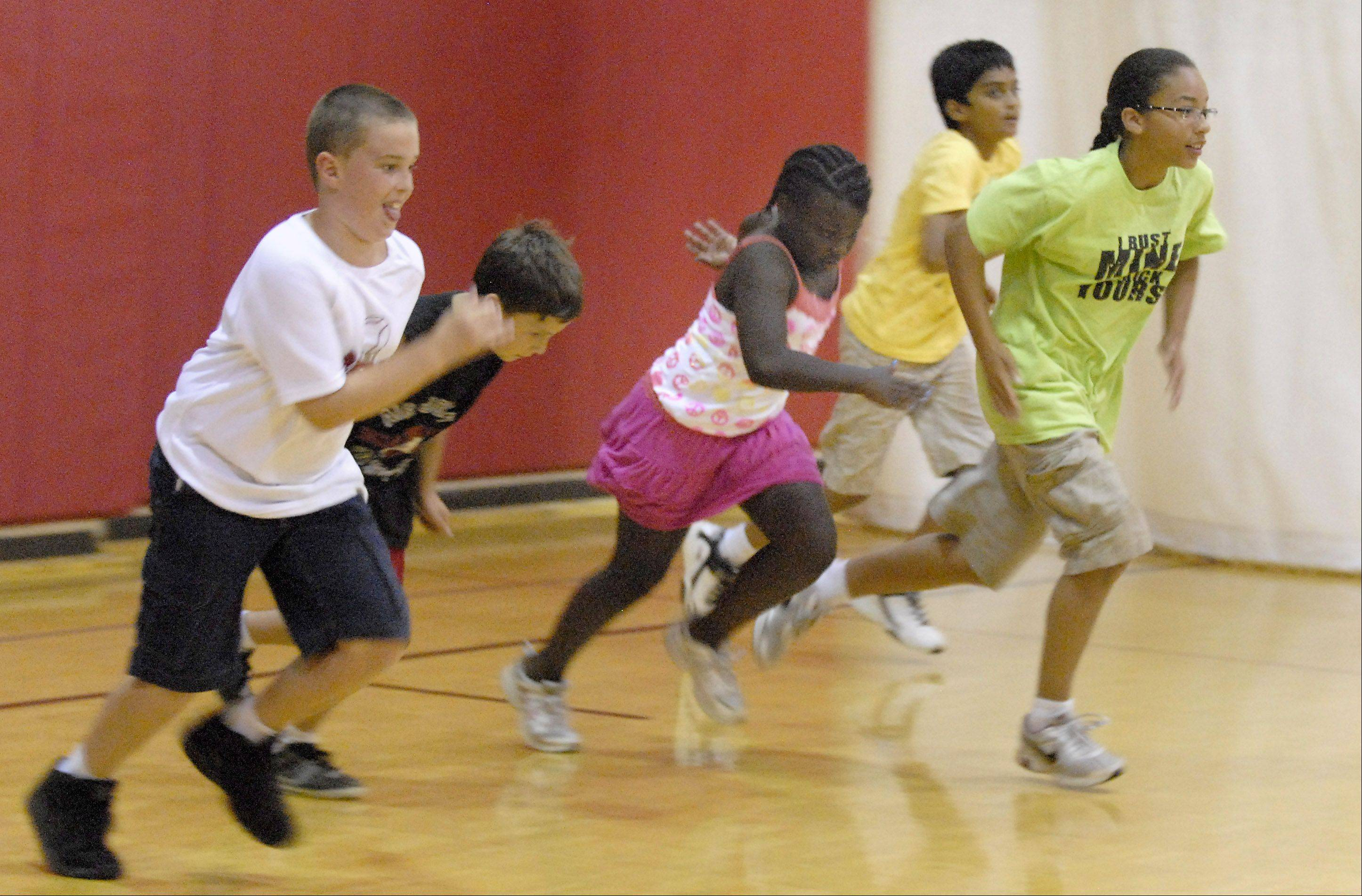 Kids at the Schaumburg Park District Day Camp work up a sweat in the air-conditioned gym. Normally in hot weather they alternate with inside and outside activities. With temperatures over 90 degrees on Tuesday they were kept inside.