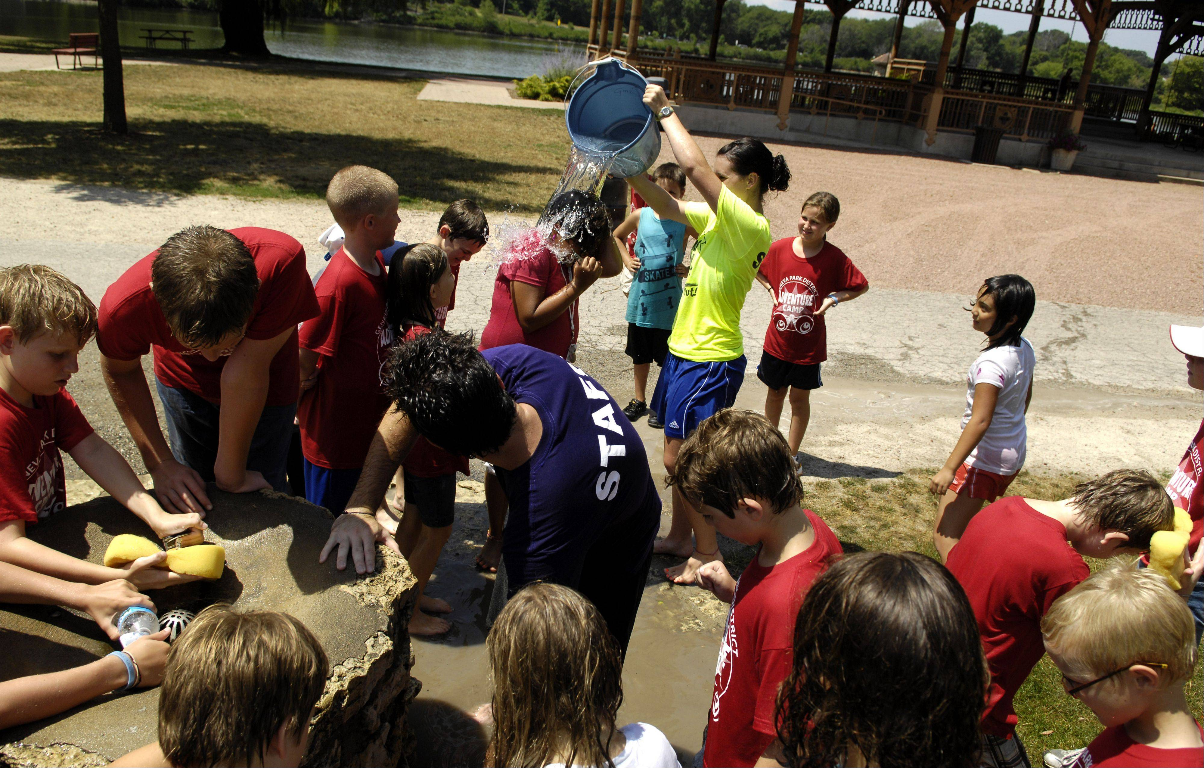 "Campers and counselors crowd around the water supply with temperatures in the mid 90's Tuesday as kids from the Geneva Park District's ""Adventure Camp"" cool off at Pottawatomie Park in St. Charles."