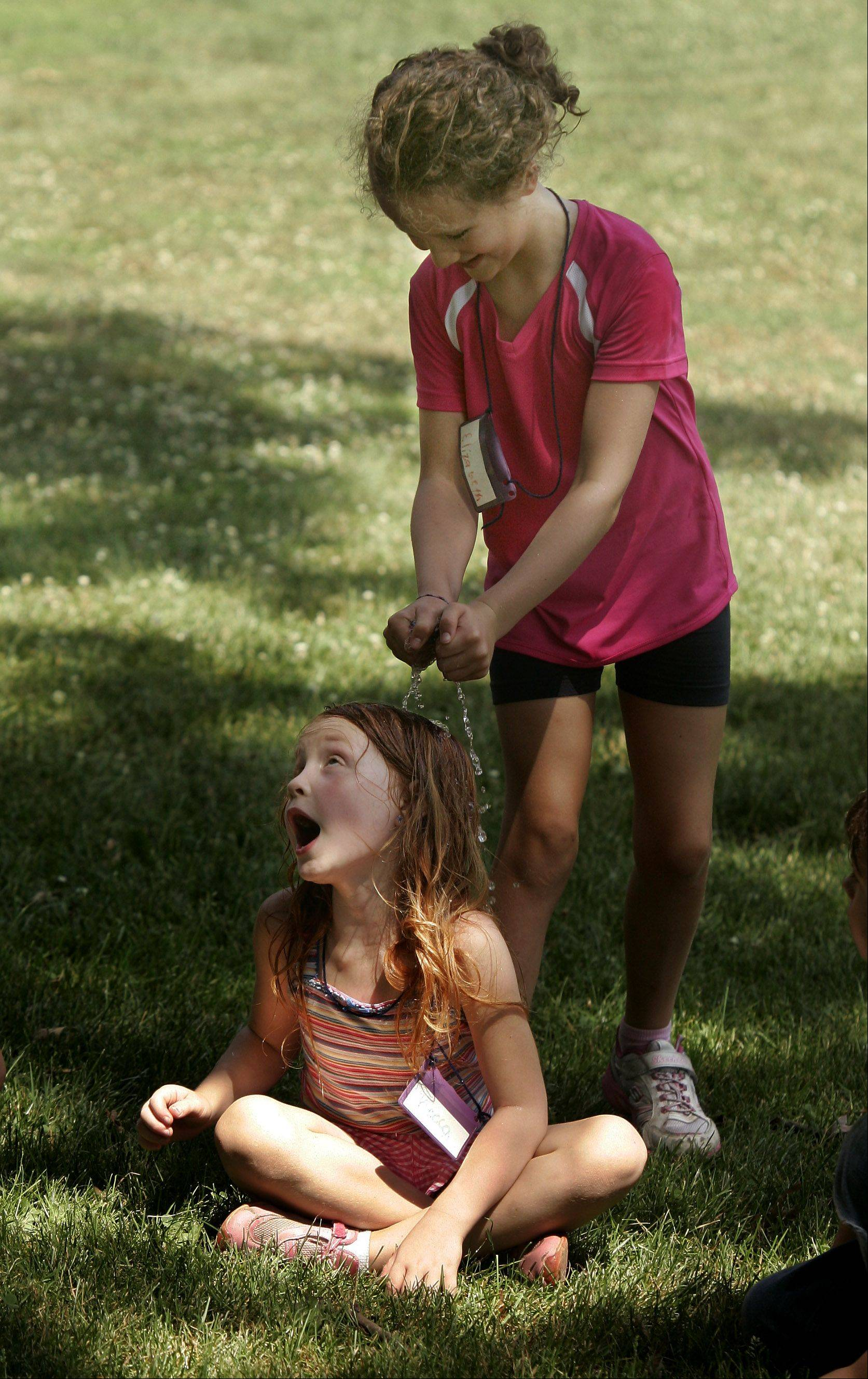 "Elizabeth Klann, 7, douses Rebecca Runyan, 6, in a game of ""Drip, Drip, Drench"" during Lake County Forest Preserve's Young Naturalists Day Camp Tuesday at Van Patten Woods in Wadsworth. The game was a hot weather substitute for ""Duck, Duck, Goose."""