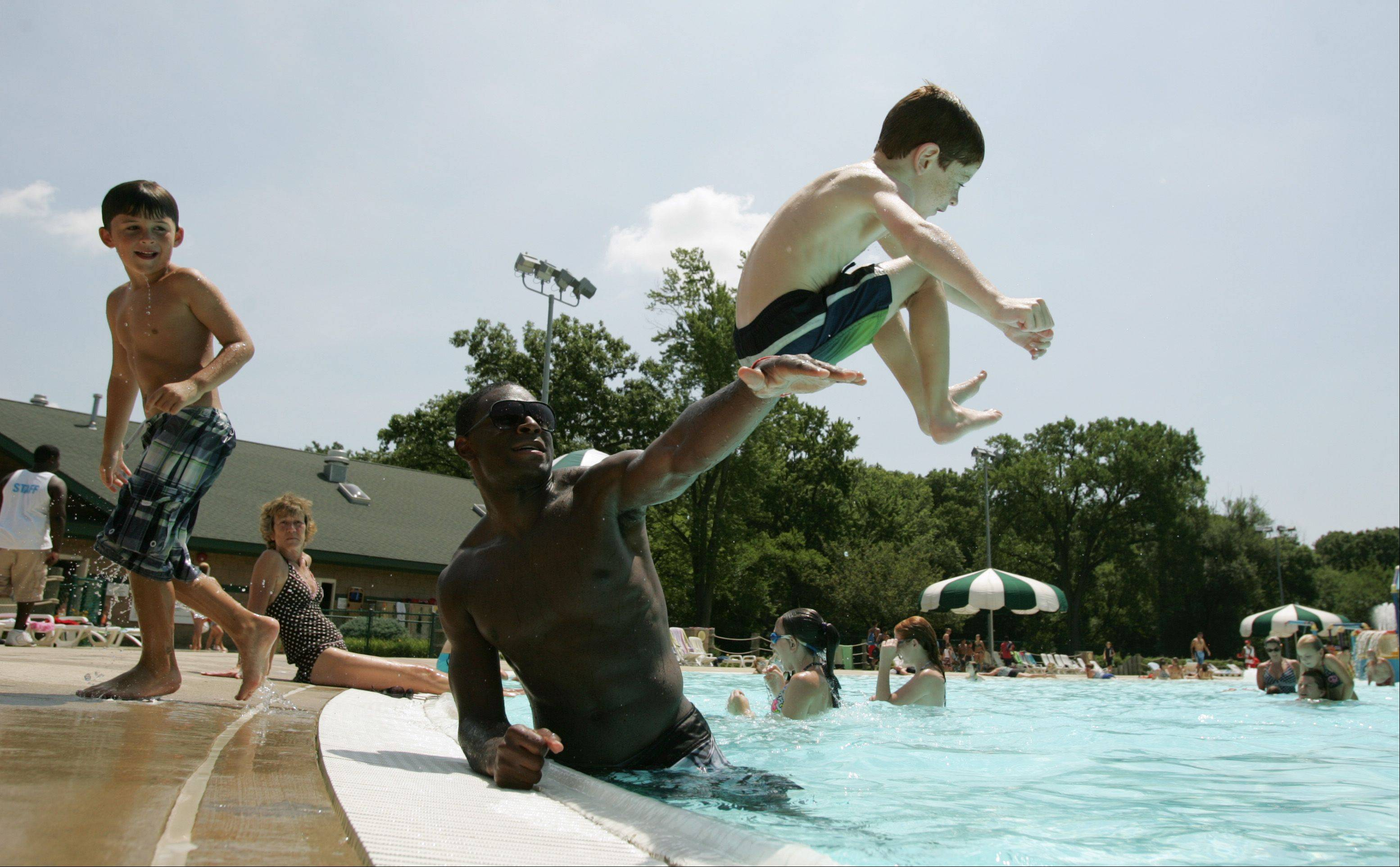 Elgin Parks and Recreation Department summer camper Jack Steskal, 7 soars over the outstretched arm of camp counselor Josh Smith Tuesday at Wing Park Family Aquatic Center in Elgin. Both Smith and Steskal are from Elgin.
