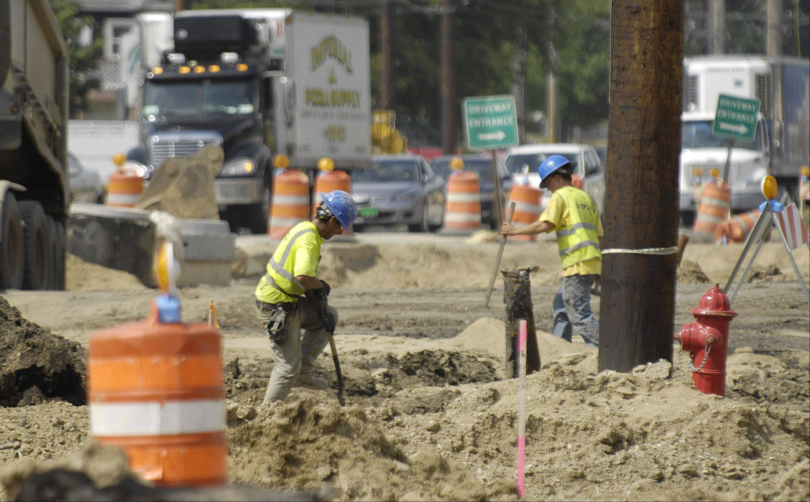 Construction workers wear heavy clothing as they continue work on Route 47 in Huntley in the heat Monday.
