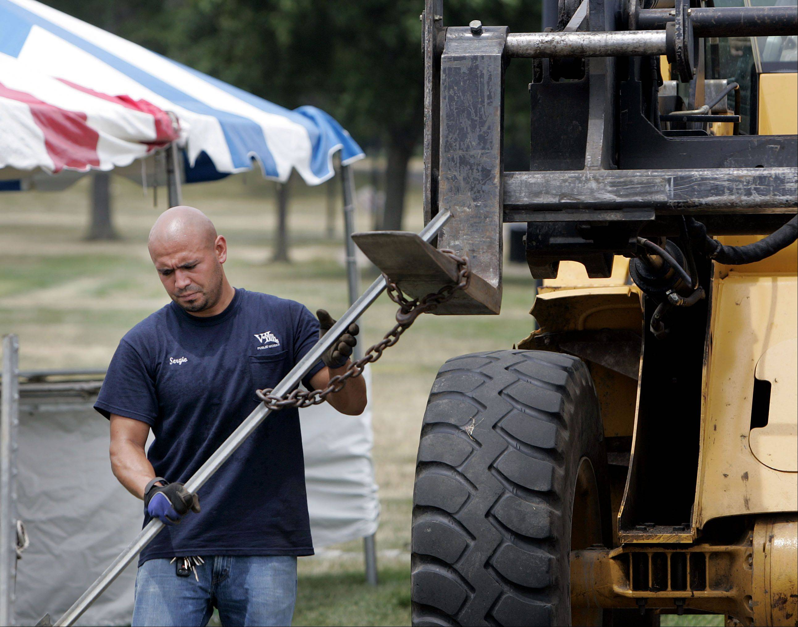 Sergio Soto, a Vernon Hills Public Works employee, works in Century Park Monday following Vernon Hills' Summer Celebration.