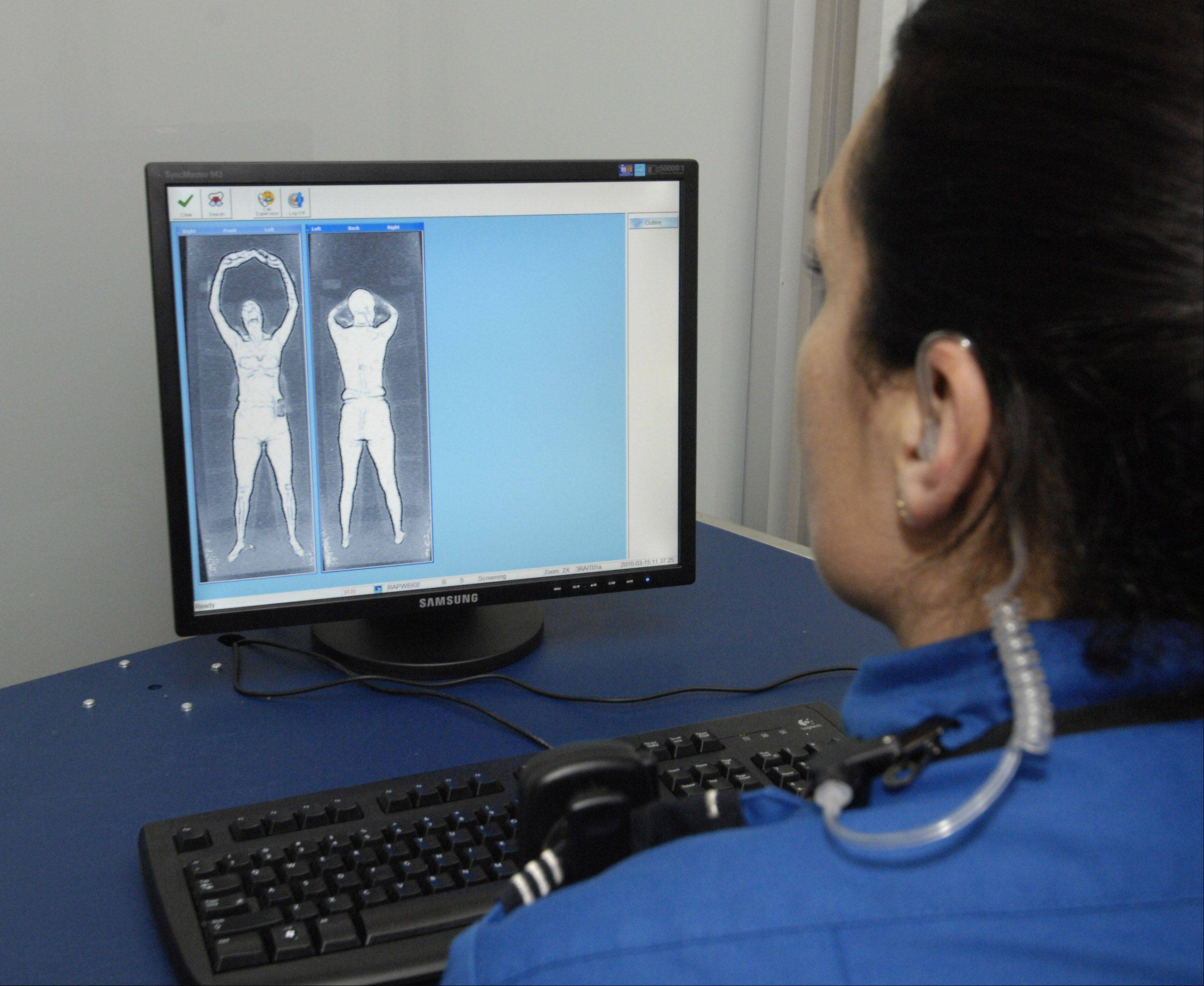 A TSA employee at O�Hare views the images from the full body scanner in March 2010. The whole body imaging machines have sparked outrage among passengers and privacy advocates.