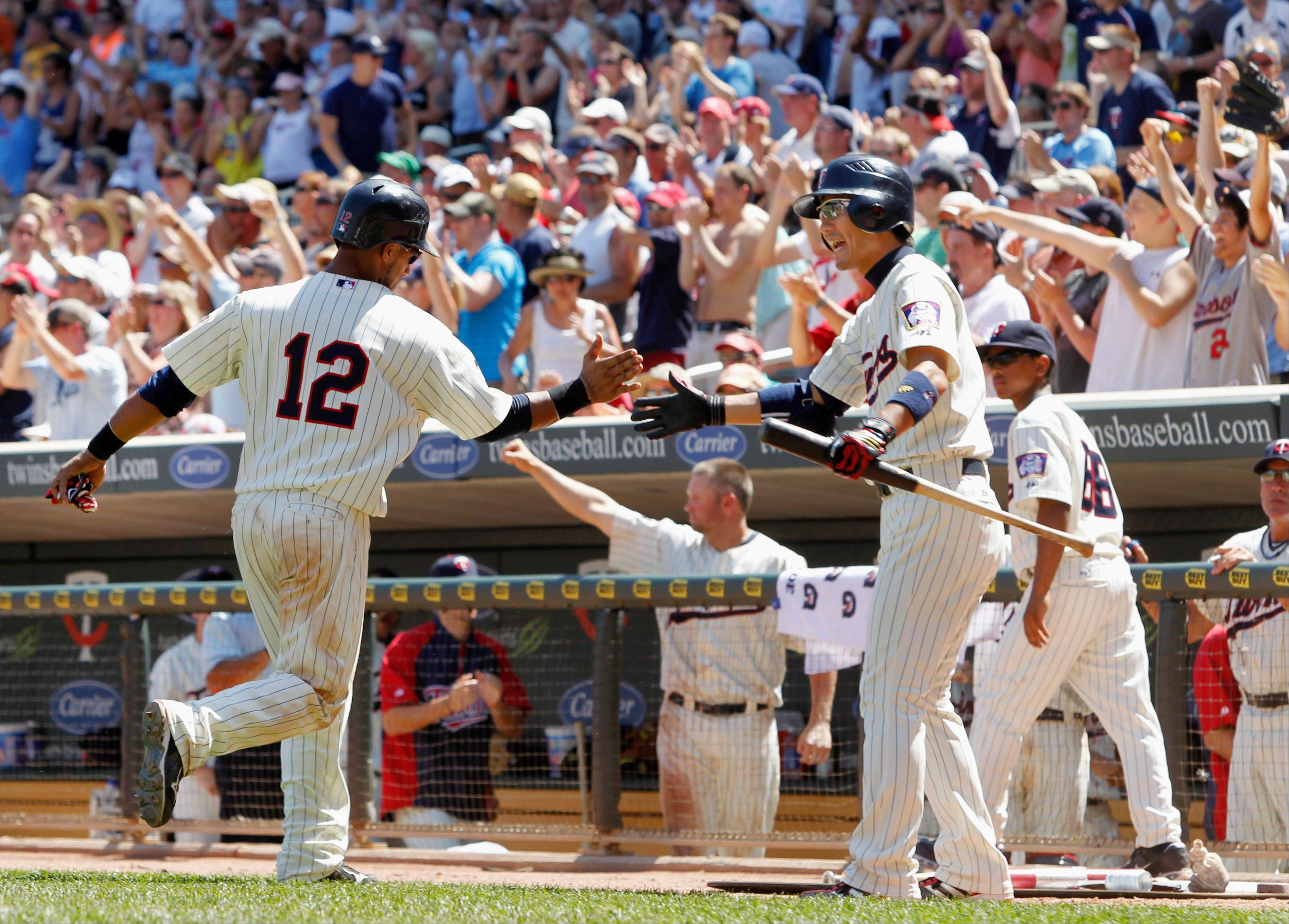 The Minnesota Twins� Alexi Casilla, left, is congratulated by teammate Tsuyoshi Nishioka after scoring the go-ahead run on Danny Valencia�s single to take the lead against the Cleveland Indians during the eighth inning on Wednesday in Minneapolis. The Twins defeated the Indians 7-5.