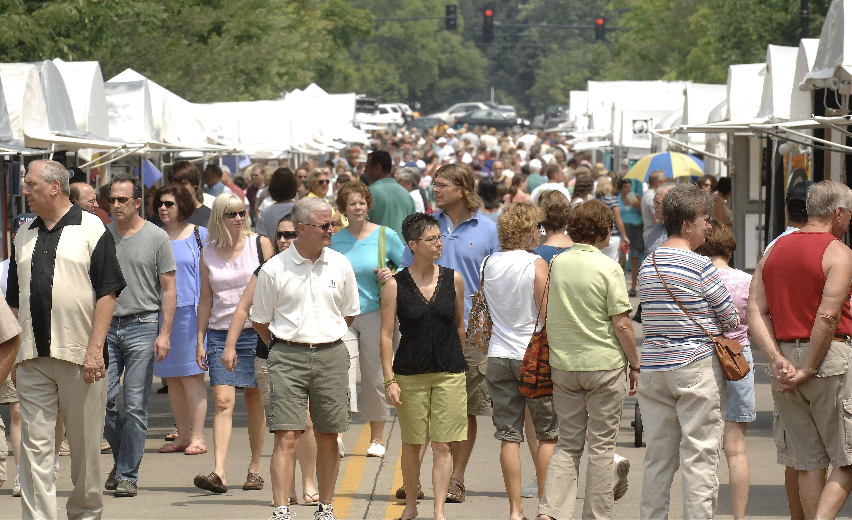 Third Street in downtown Geneva is packed by shoppers attending the seventh annual Geneva Arts Fair. The fair features 150 juried artists and their work.