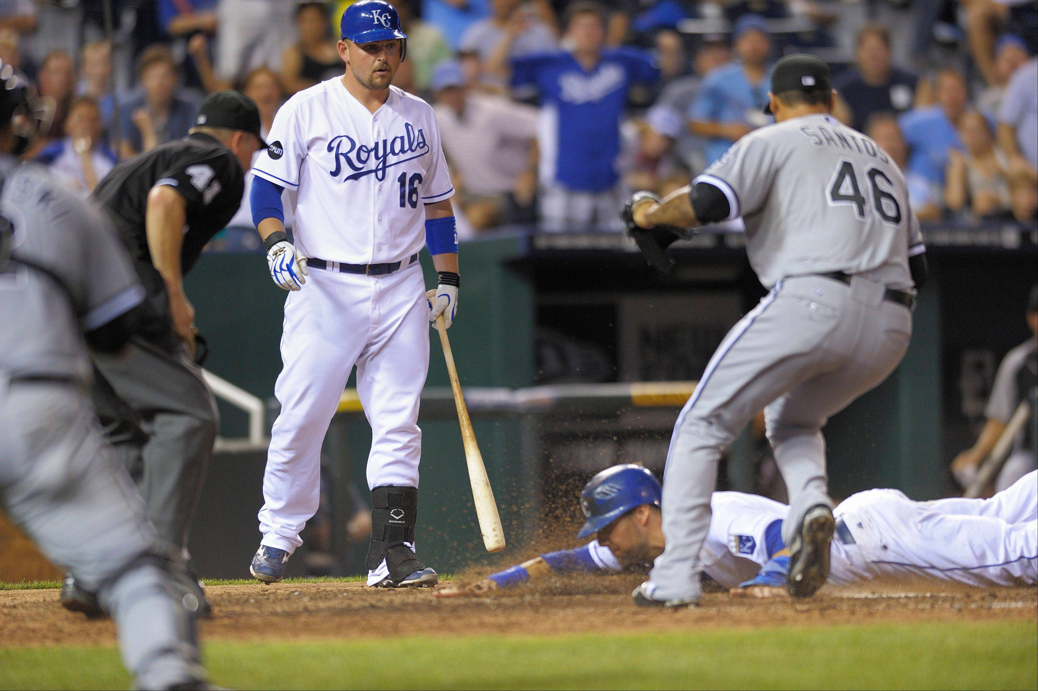 The Royals' Alex Gordon, bottom right, steals home on a wild pitch from White Sox relief pitcher Sergio Santos to Billy Butler with umpire Jerry Meals watching with two out in the bottom of the 11th inning to win 2-1 Wednesday night.