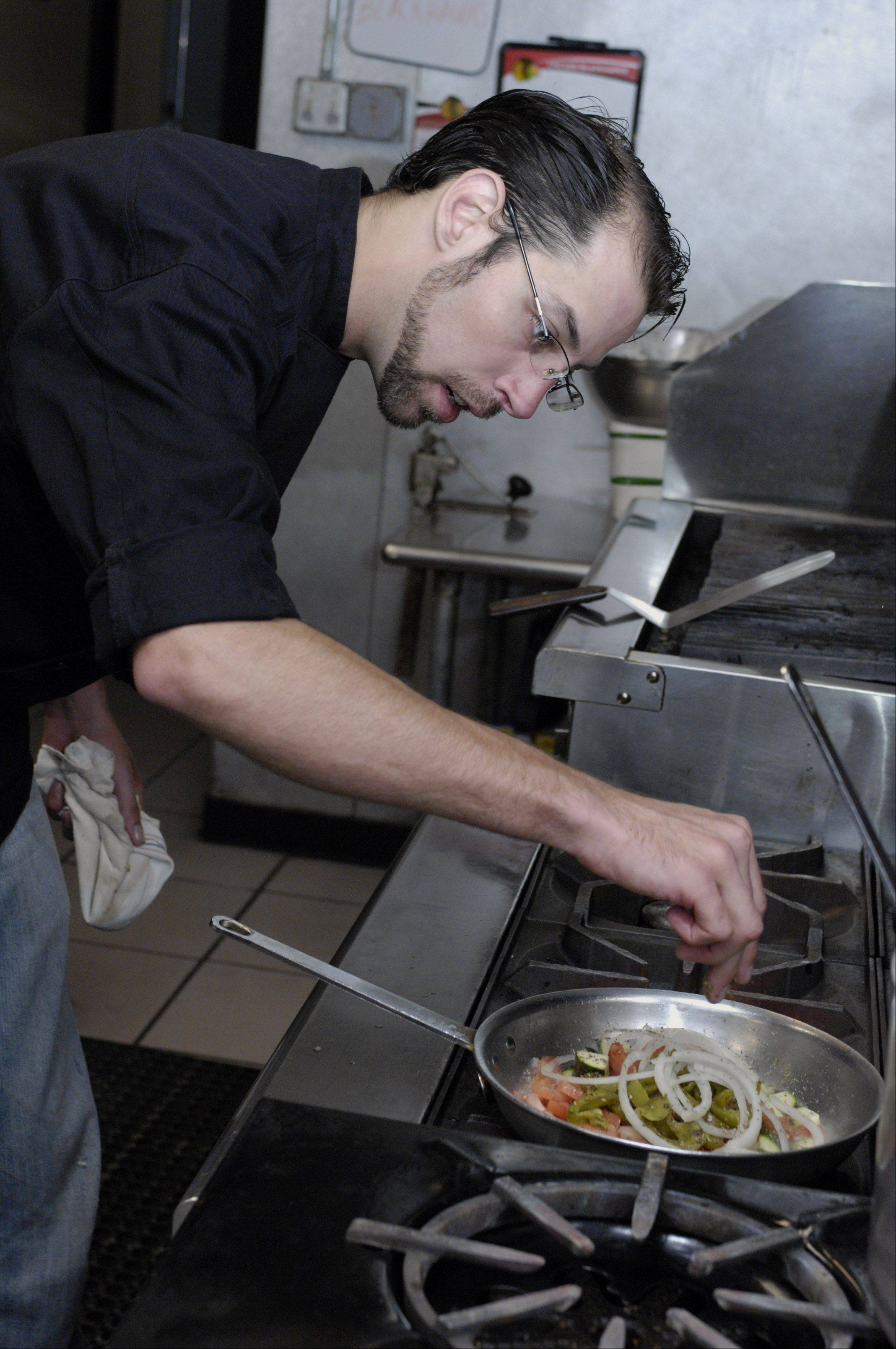 Chef Trevor McGrath seasons his Bridgeport Pasta, a favorite dish among diners at Bella Luna in Glendale Heights.