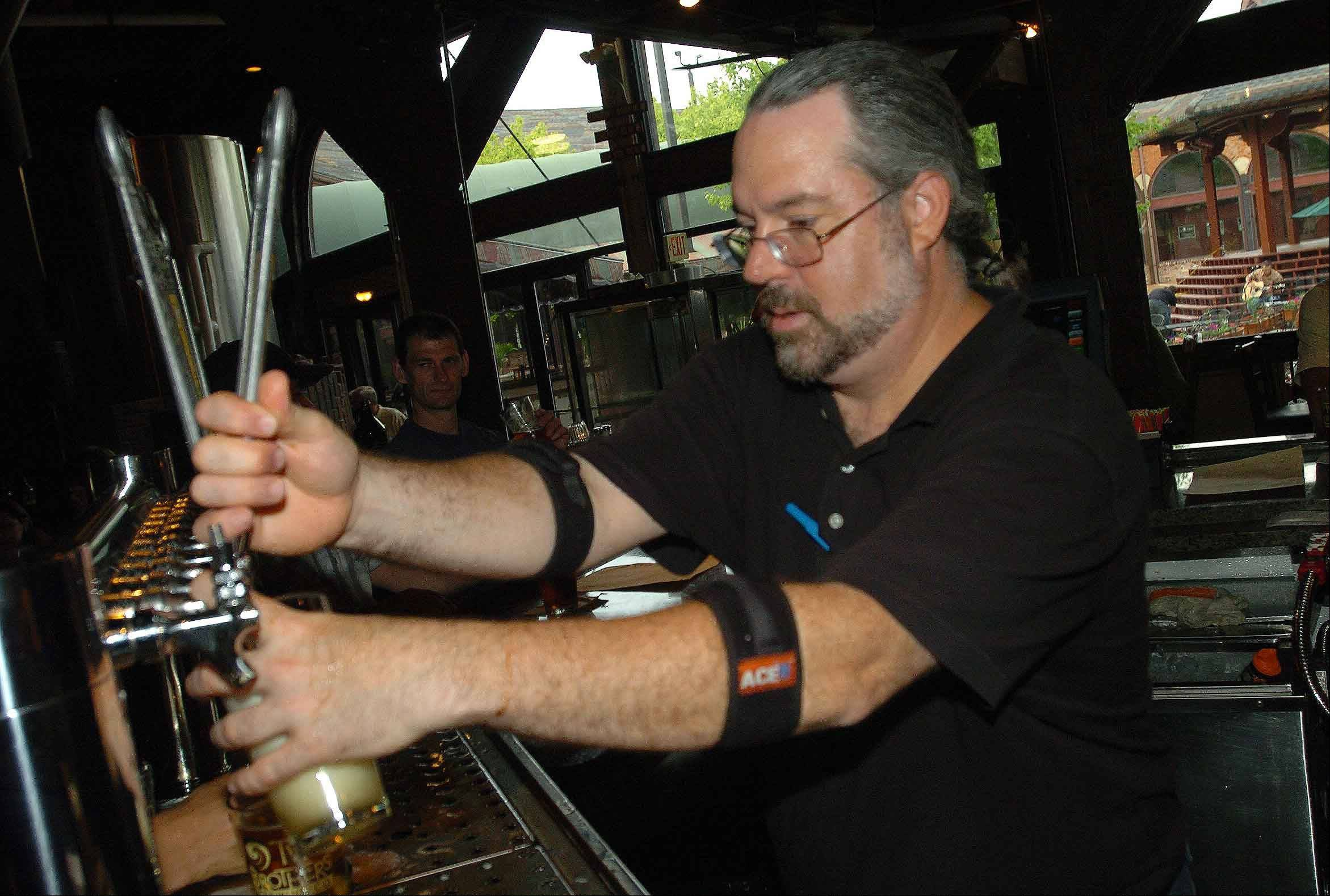 John Strunk taps a beer at Two Brothers Roundhouse in Aurora.
