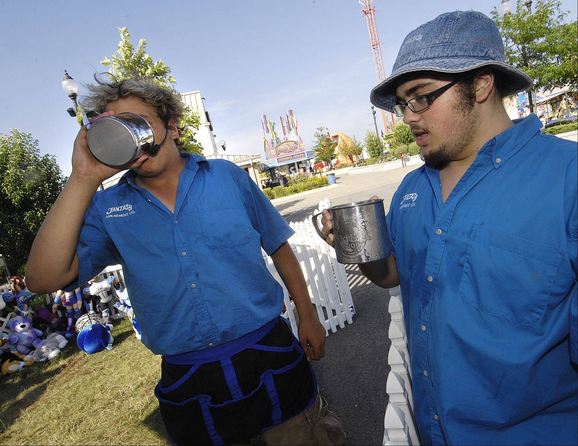 Fantasy Amusements worker Nick Dus chugs his drink while Zachary Romano lets his settle before taking another slug of a mixture of orange and grape drinks at the Hammer Slammer game during the first day of the Kane County Fair Wednesday in St. Charles.